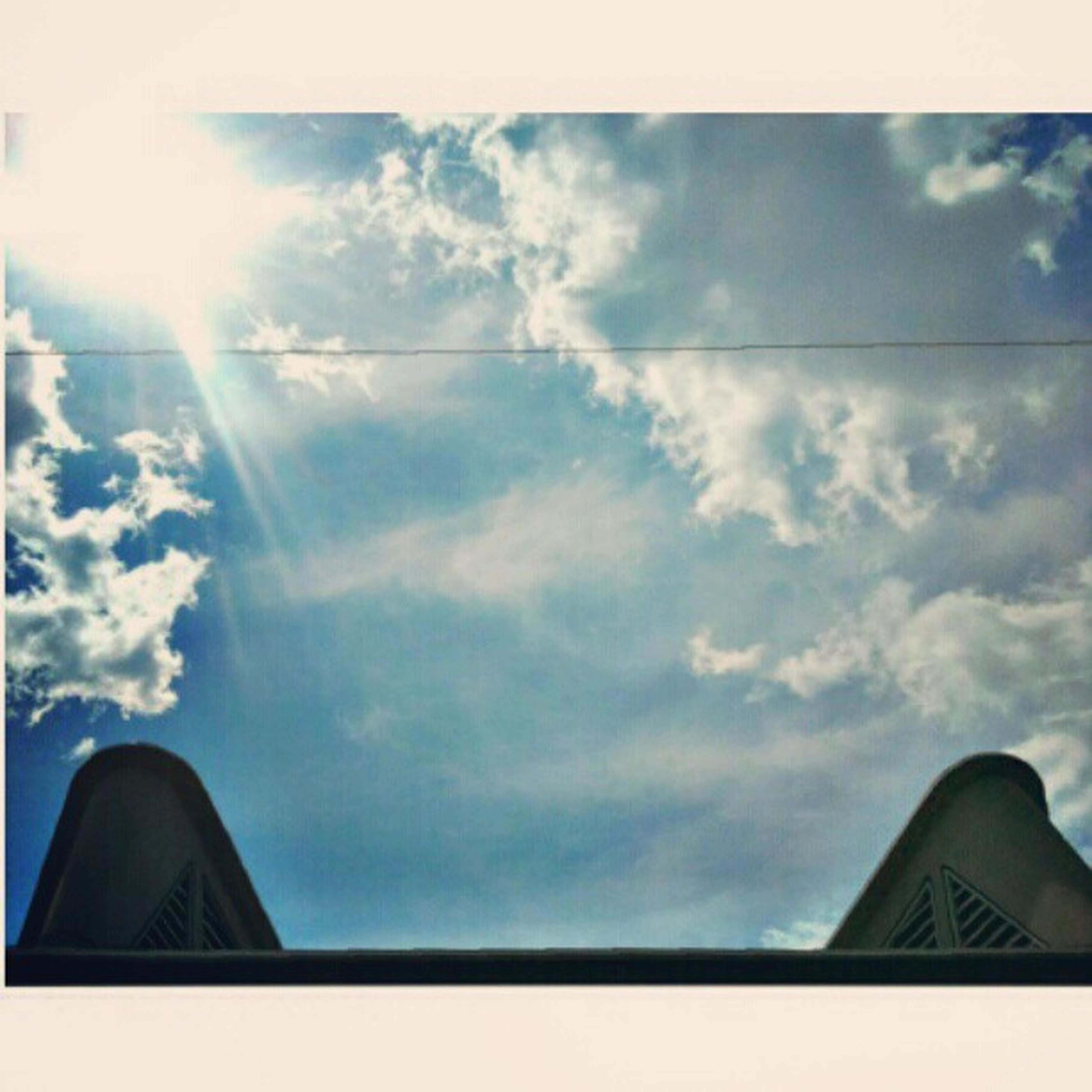 sky, low angle view, cloud - sky, building exterior, architecture, built structure, cloud, cloudy, high section, part of, blue, outdoors, day, sunlight, nature, no people, cloudscape, window, cropped, house