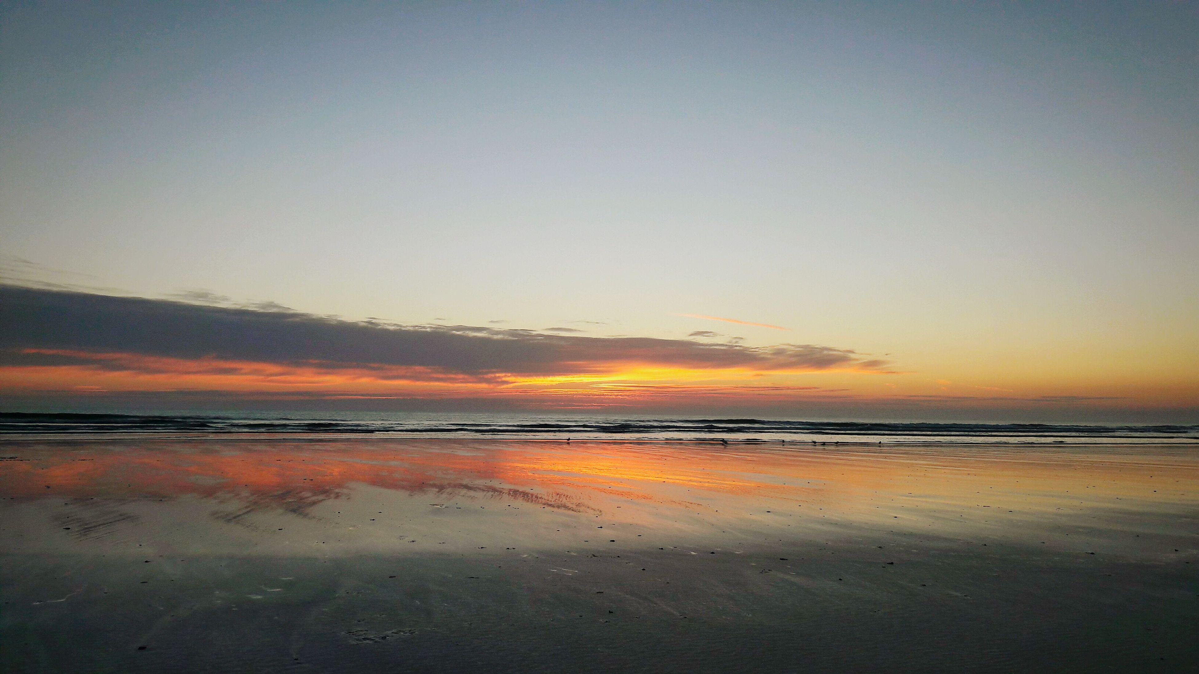 sunset, sea, beach, water, horizon over water, scenics, tranquil scene, tranquility, beauty in nature, idyllic, calm, shore, orange color, reflection, nature, sky, sun, seascape, remote, coastline, ocean, non-urban scene, vacations, no people, waterfront, majestic, solitude, cloud - sky, romantic sky