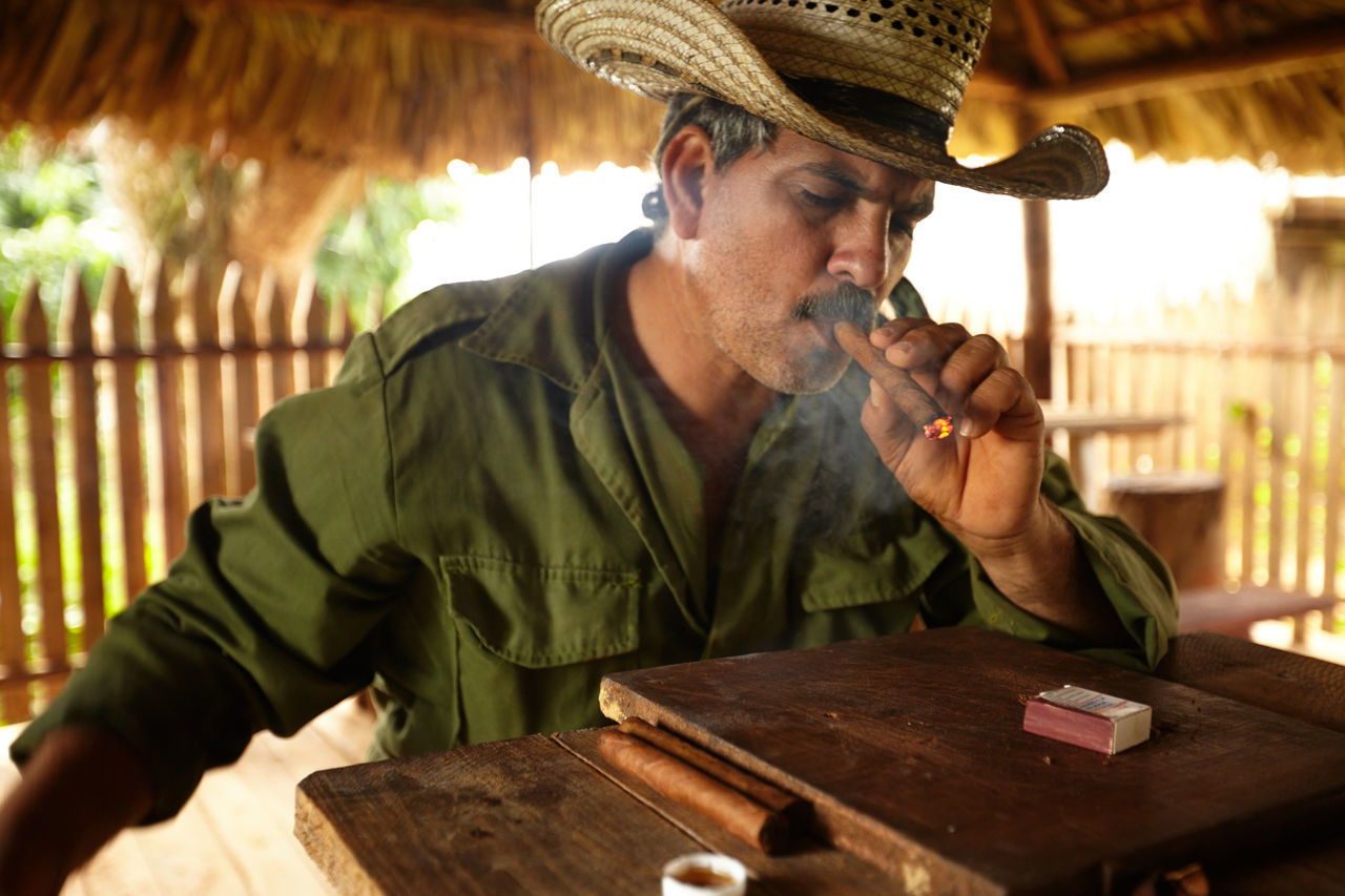Addiction Adult Adults Only Bad Habit Casual Clothing Countryside Cuban Cigar Cuban Life Day Headshot Holding Indoors  Men One Man Only One Person Only Men People Real People Sitting Table Tobacco Leaf Wood - Material