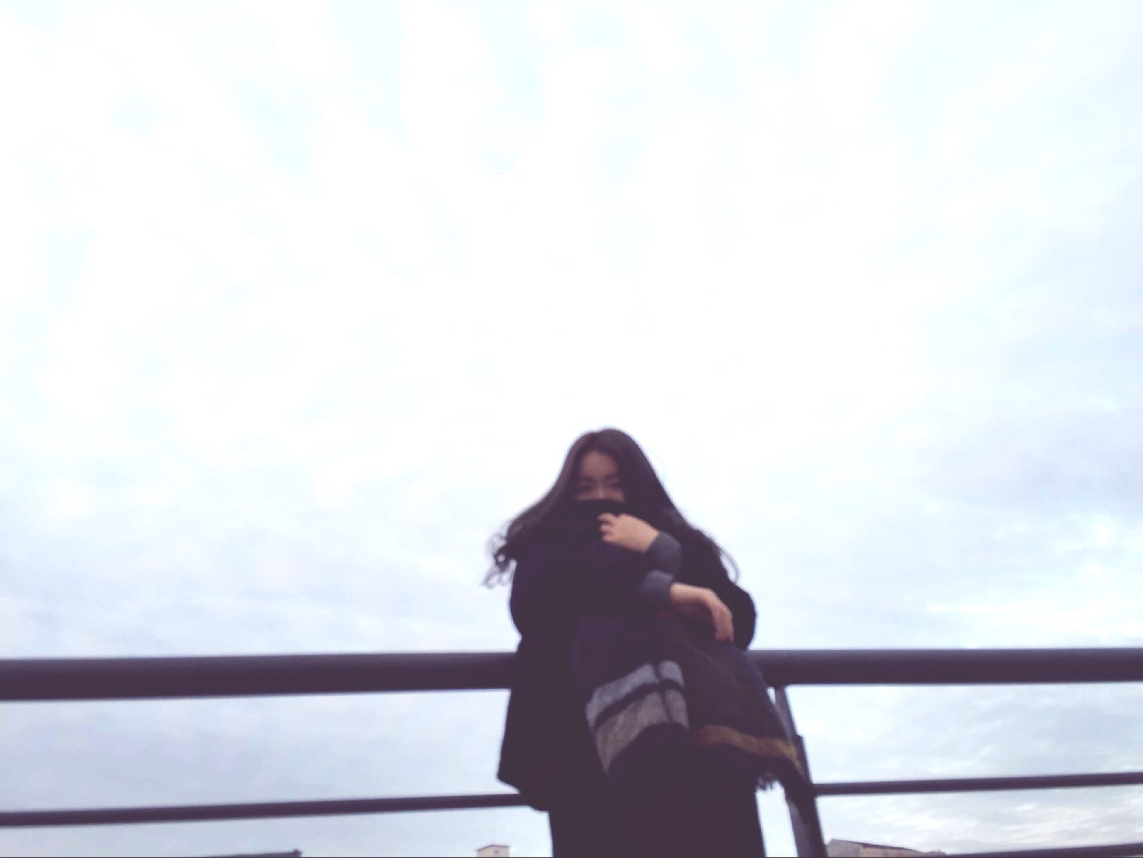 waist up, sky, lifestyles, standing, low angle view, three quarter length, leisure activity, young adult, casual clothing, railing, headshot, day, cloud - sky, rear view, outdoors, side view, looking away, cloud
