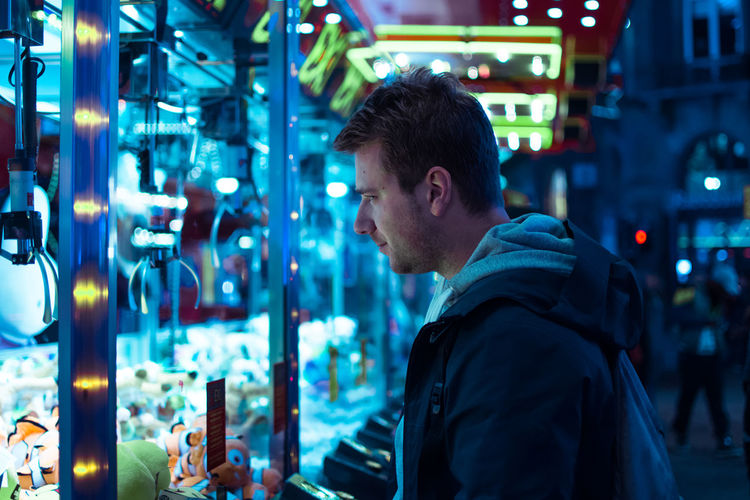 Portrait of a man with light reflections on her face at the carnival Carnival Casino Adult Adults Only Focus On Foreground Illuminated Lifestyles Machones Men Neon Night One Person Outdoors People Real People Side View Standing Young Adult Young Men
