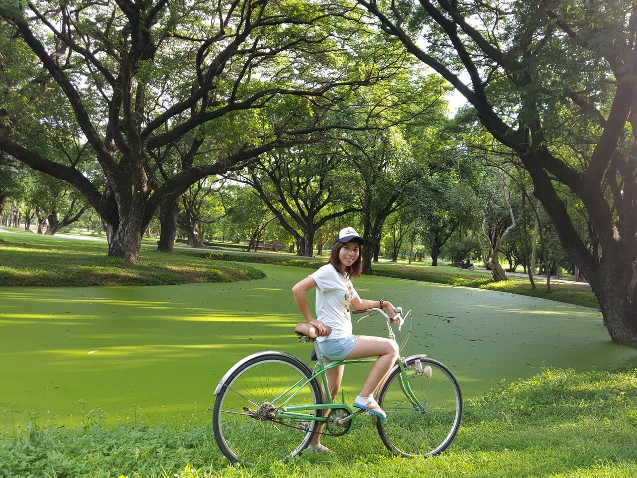 bicycle, tree, grass, transportation, smiling, cycling, looking at camera, happiness, casual clothing, one person, day, full length, outdoors, riding, real people, leisure activity, park - man made space, green color, road, lifestyles, nature, cheerful, portrait, growth, young adult, people