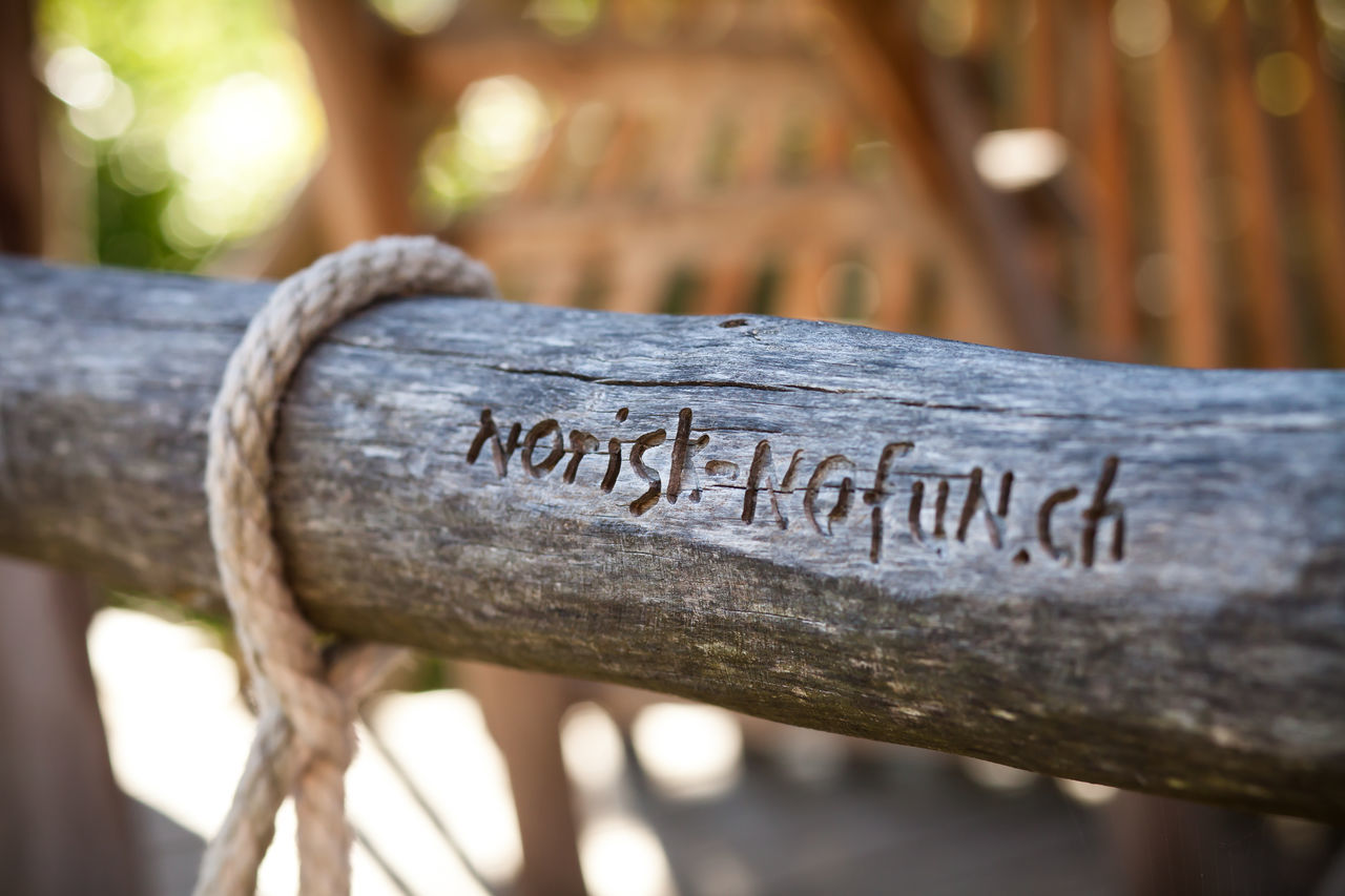 text, communication, western script, close-up, wood - material, focus on foreground, outdoors, no people, day