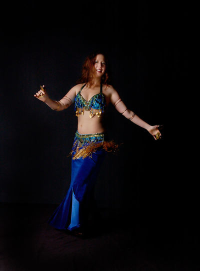 Belly Dance Belly Dancer Dance Beautiful Woman Belly Dancer Belly Dancing Bellydance Bellydancer Bellydancing Black Background Color Dancer Full Length Happiness Human Arm Limb Motion One Woman Only One Young Woman Only People Performance Portrait Smiling Standing Studio Shot
