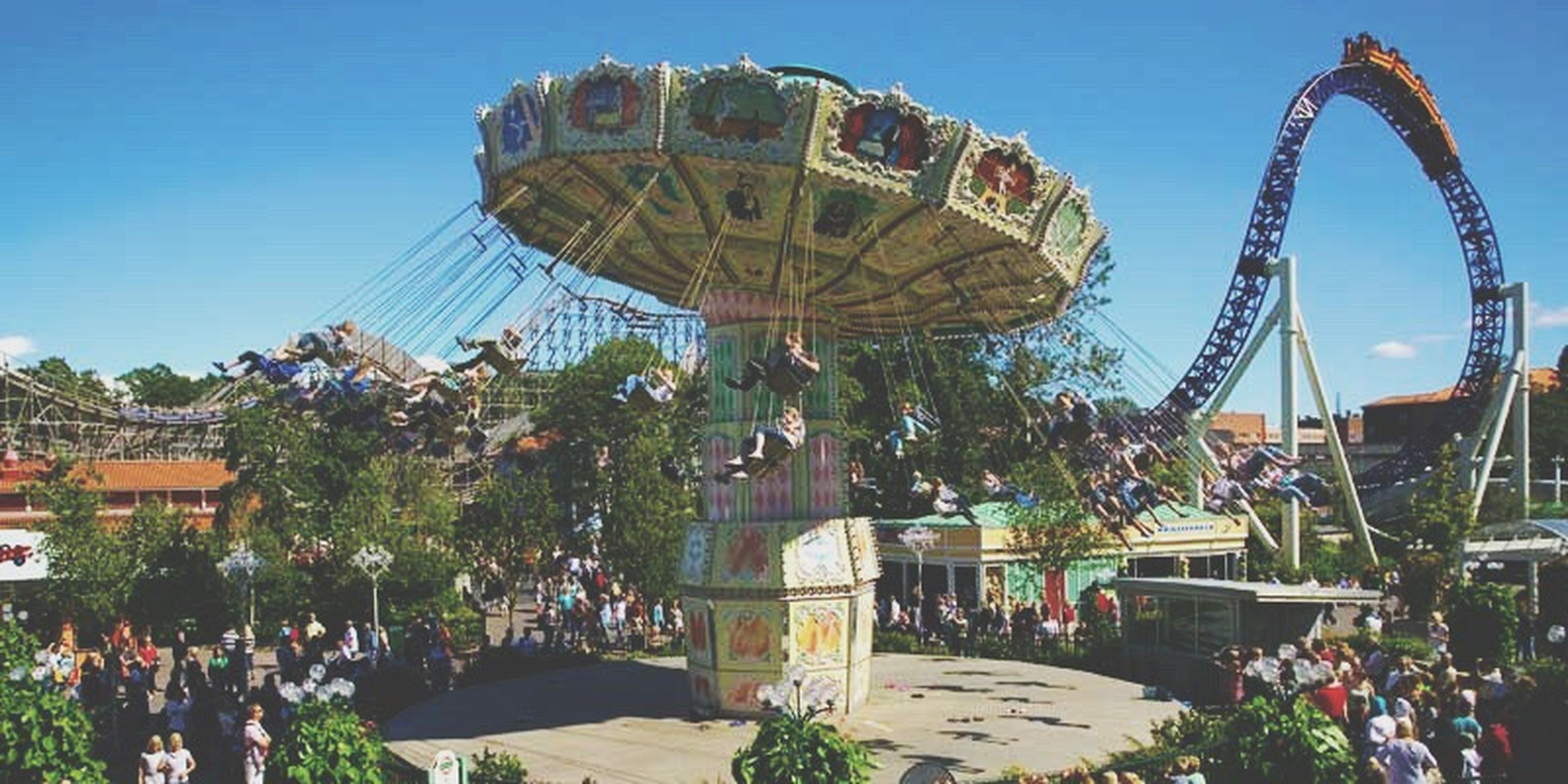 amusement park, ferris wheel, amusement park ride, arts culture and entertainment, built structure, tree, architecture, clear sky, blue, incidental people, building exterior, sky, travel destinations, tourism, leisure activity, low angle view, sunlight, park - man made space, outdoors, day