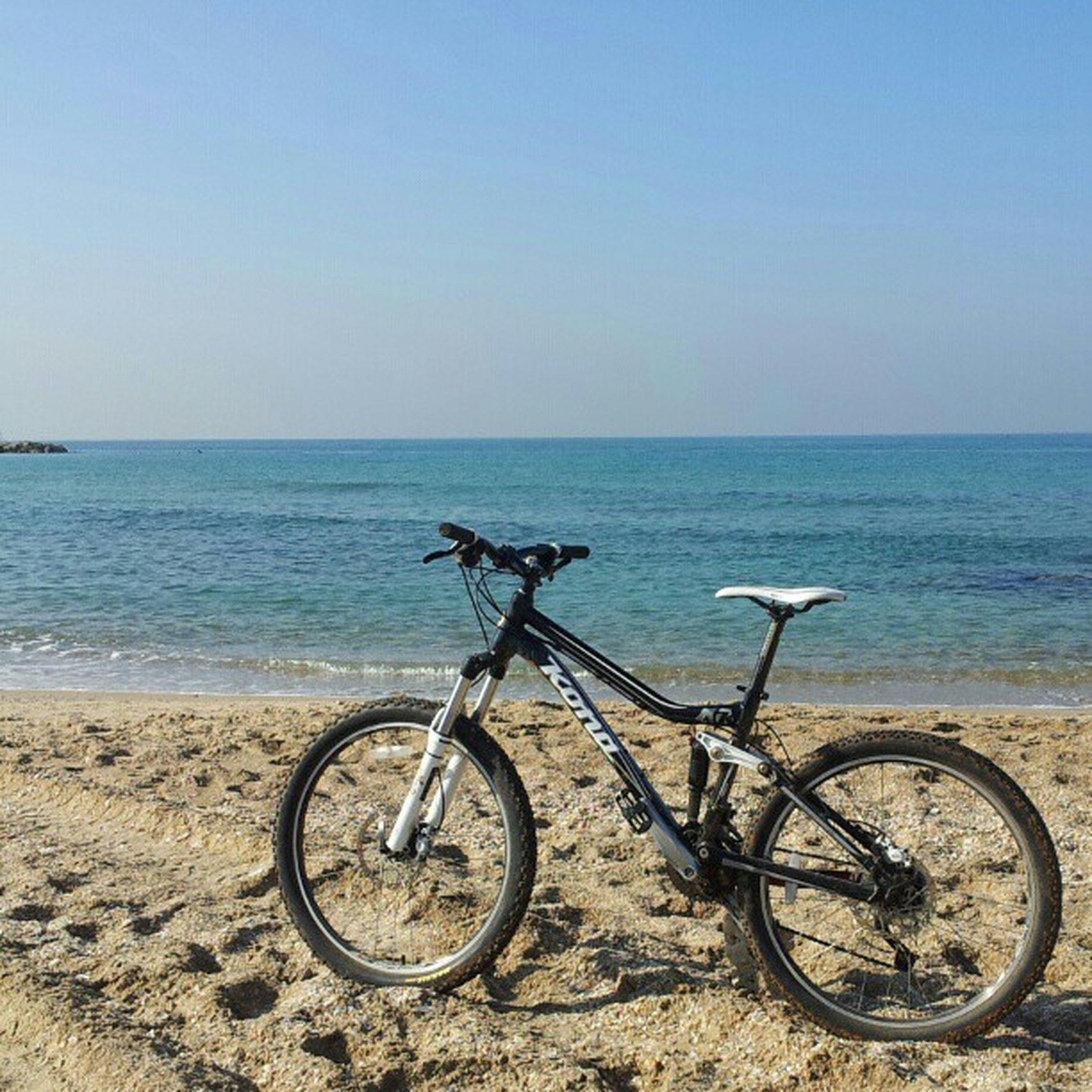 bicycle, transportation, sea, horizon over water, mode of transport, water, stationary, land vehicle, beach, parking, parked, tranquility, tranquil scene, blue, shore, copy space, beauty in nature, scenics, nature, clear sky