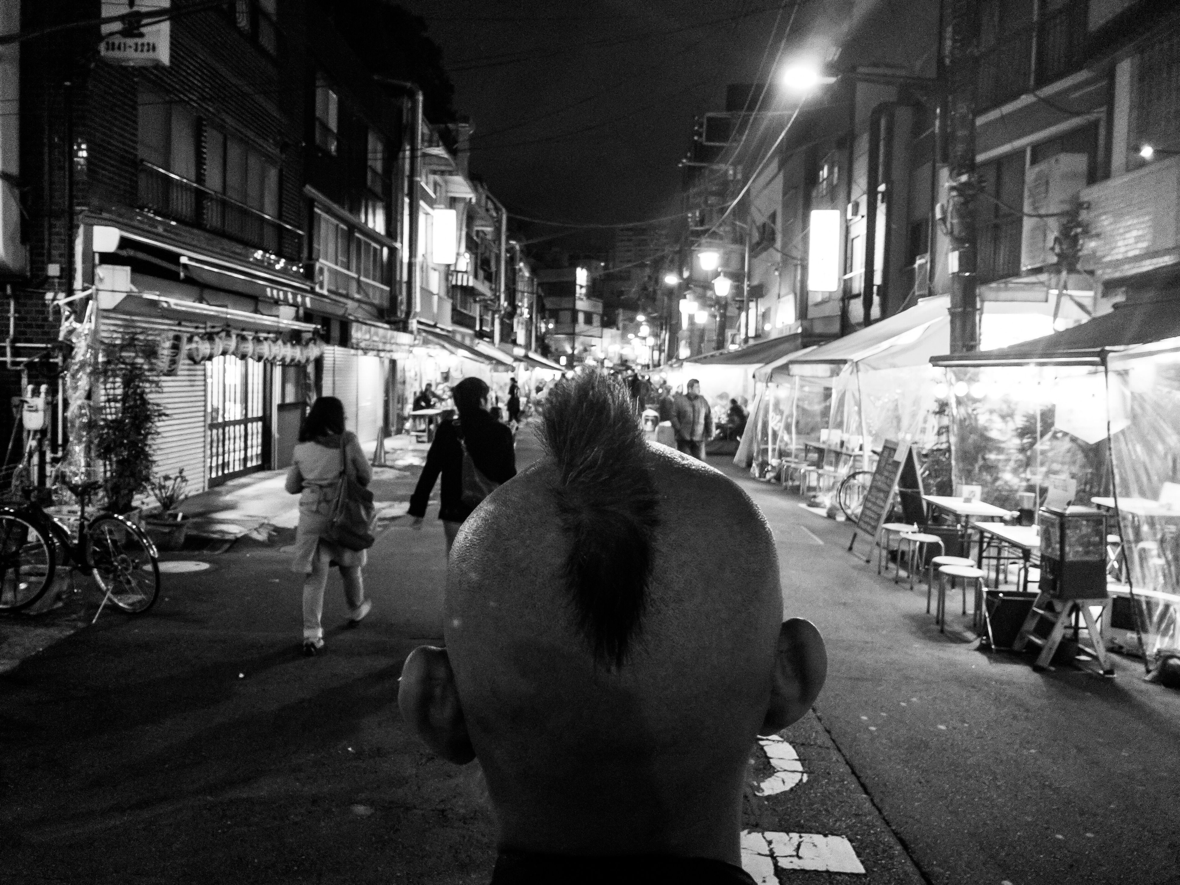 illuminated, city, only men, night, rear view, people, adults only, men, adult, real people, one person, outdoors, architecture, one man only, sky