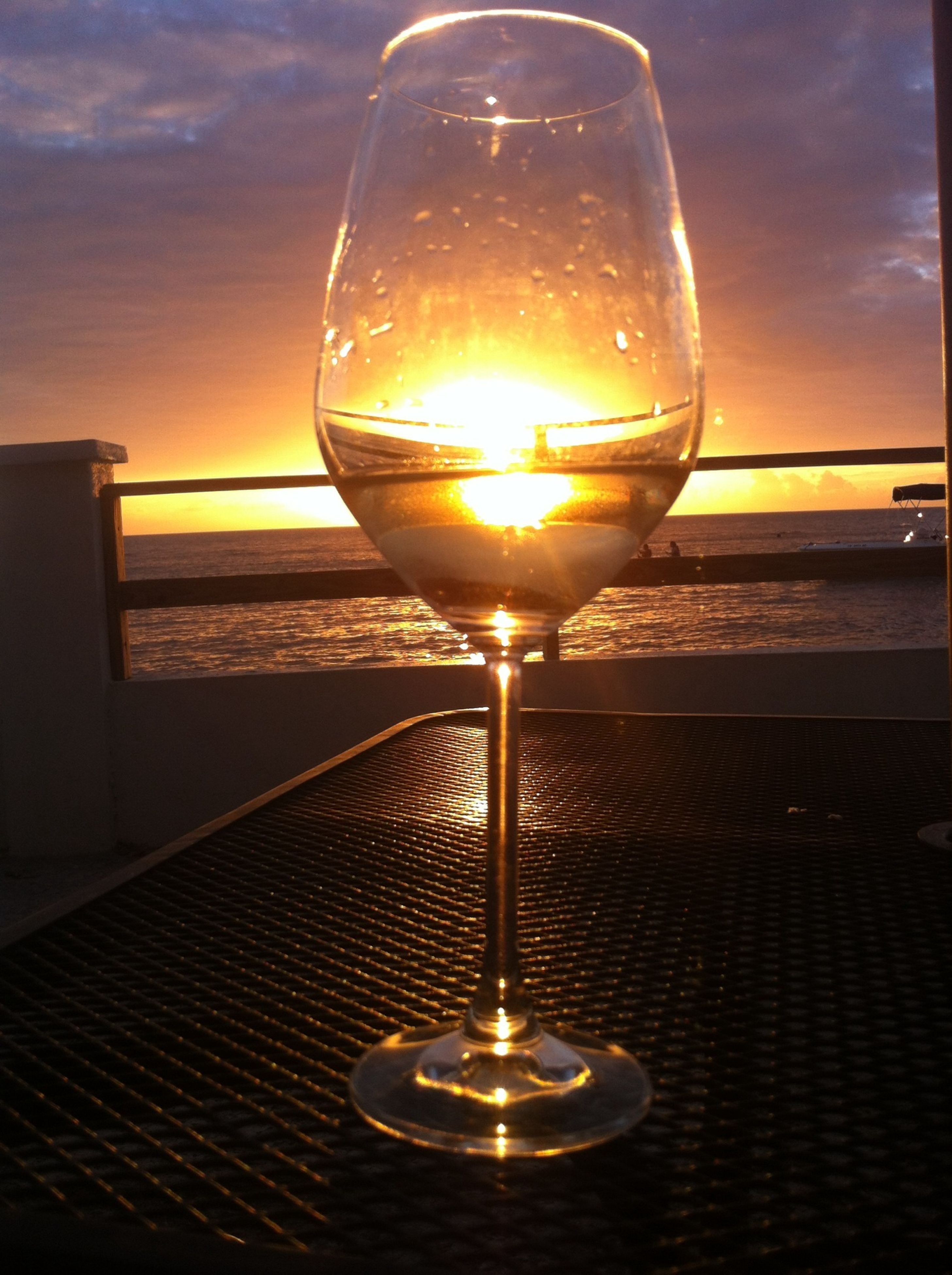 wineglass, illuminated, indoors, lighting equipment, close-up, wine, alcohol, glass - material, focus on foreground, transparent, sunset, drinking glass, drink, table, light bulb, sky, no people, refreshment, lit, glowing