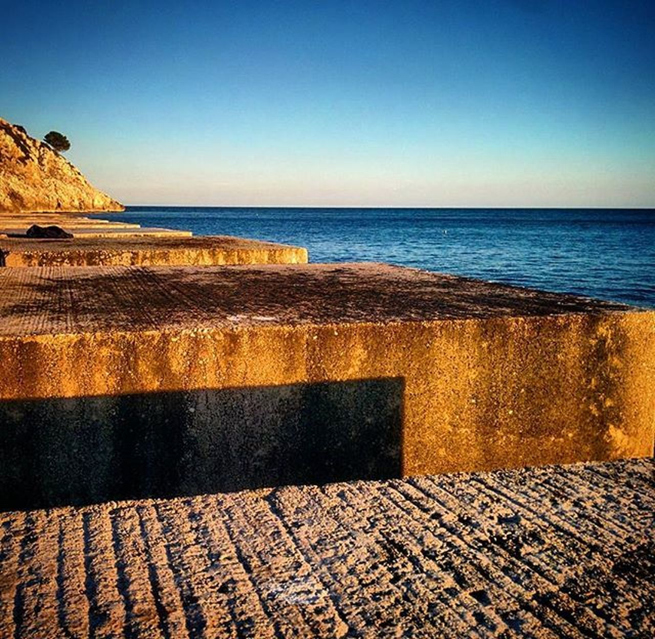 sea, horizon over water, water, beach, scenics, history, rock - object, nature, outdoors, travel destinations, no people, beauty in nature, tranquility, sky, day, vacations, sand, groyne, clear sky, wave
