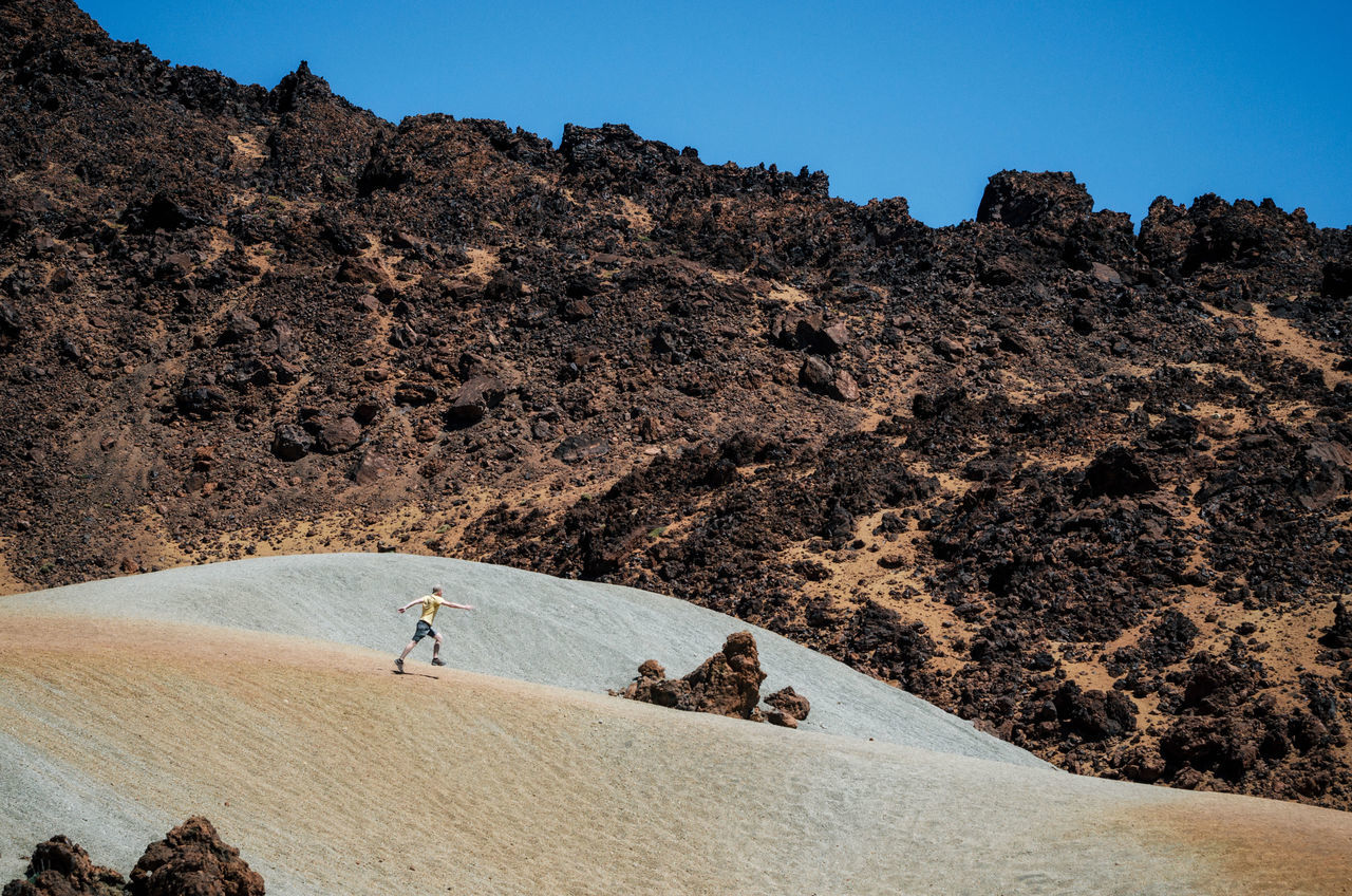 A man in a cap runs along the sand dunes against the backdrop of the mountains. The crater of Teide volcano. Teide National Park, Tenerife, Canary Islands, Spain. Adventure Arid Climate Beauty In Nature Crater Day Landscape Mars Mountain Nature One Person Outdoors People Real People Rock - Object Scenics Teide Volcanic Landscape Volcano The Great Outdoors - 2017 EyeEm Awards Let's Go. Together.