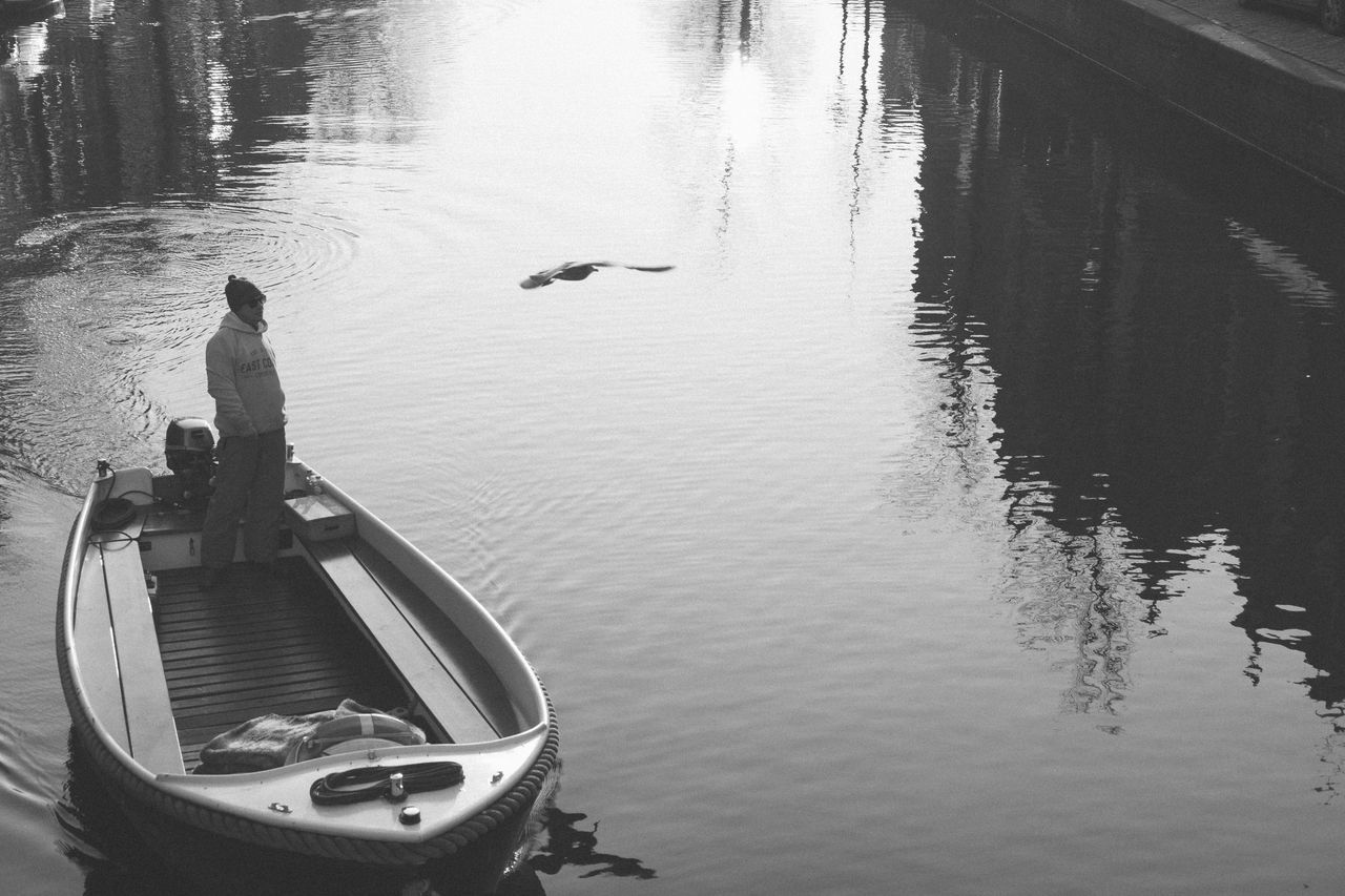 water, reflection, transportation, day, lake, mode of transport, bird, nature, animals in the wild, outdoors, men, real people, one person, swan, nautical vessel, one man only, people