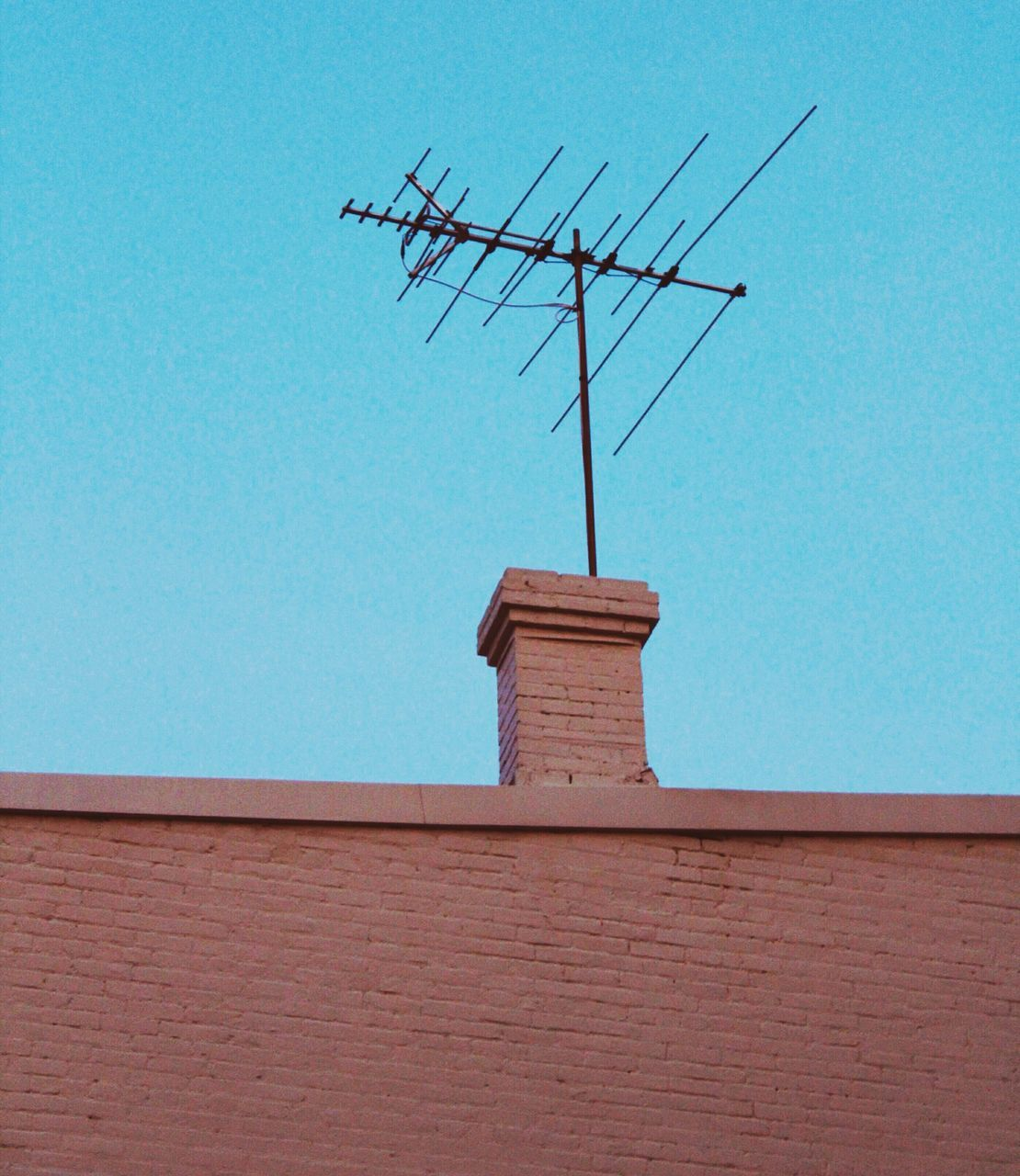 roof, architecture, built structure, antenna - aerial, building exterior, communication, no people, day, low angle view, television aerial, telecommunications equipment, weather vane, outdoors, tiled roof, technology, clear sky, sky
