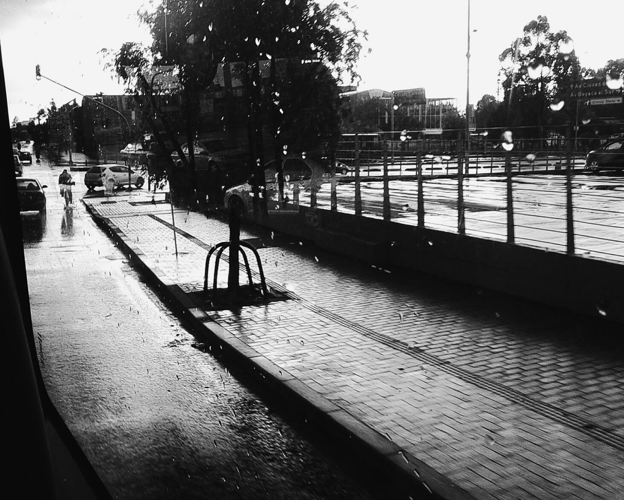 Wet Sidewalk And Road Seen Through Bus Window During Monsoon
