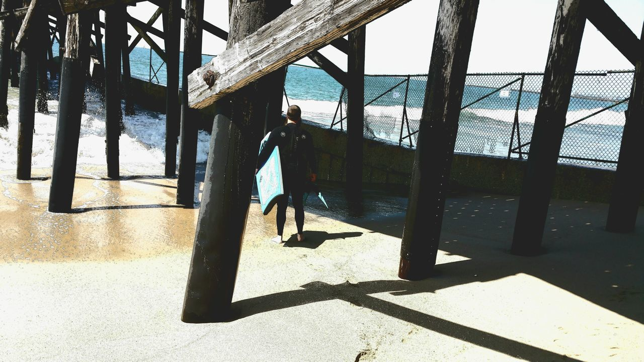 Surf's Up Under The Pier Architecture Outdoors One Person Lifestyles Sunlight Shadow Check This Out People Fine Art Photgraphy Interesting Perspective  Scenics Light And Shadow Atmospheric Mood Abstract Ocean Decisions Anticipation Joy Lovin It Life Design