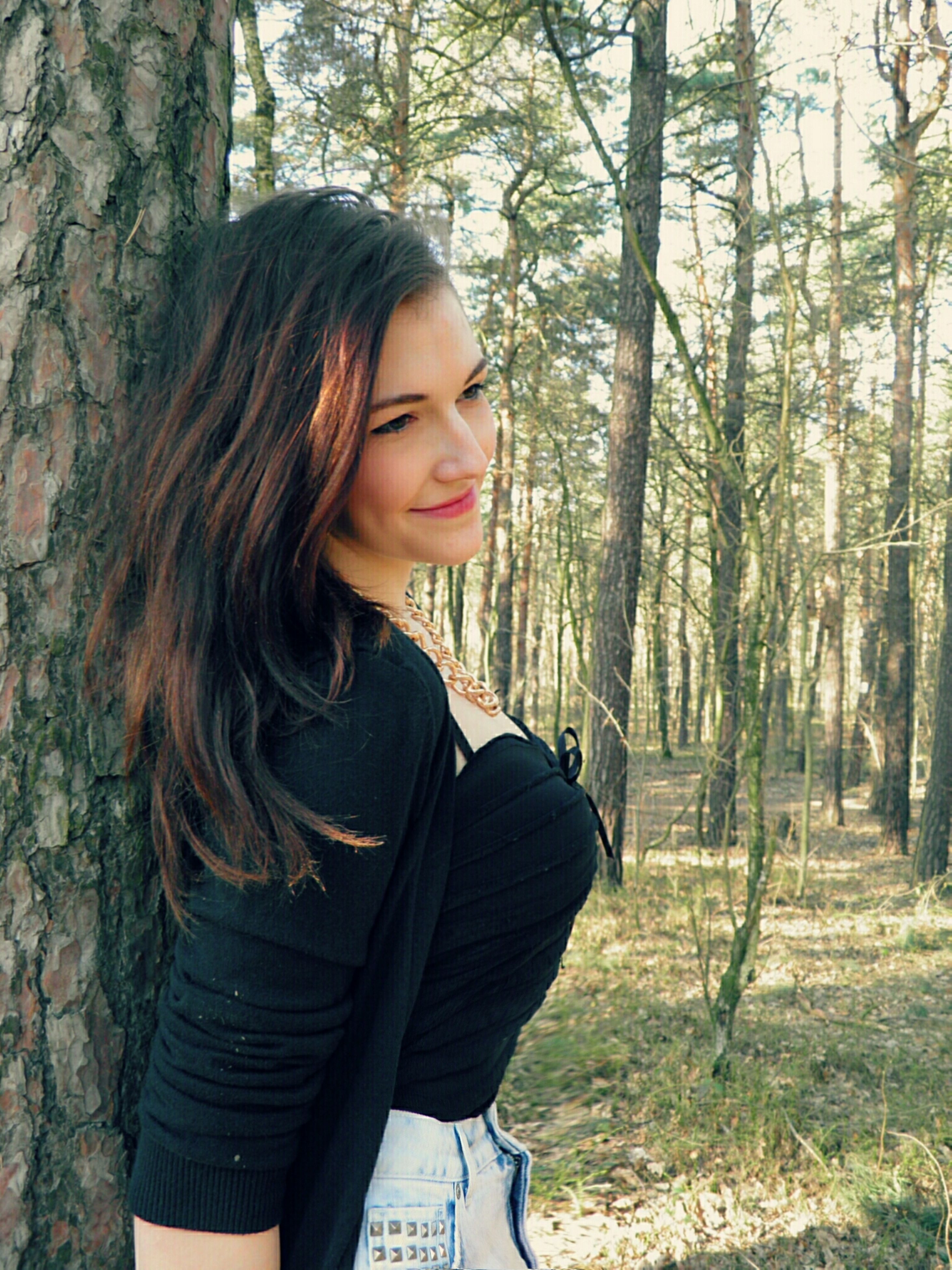 young adult, tree, young women, long hair, person, lifestyles, looking at camera, portrait, casual clothing, leisure activity, forest, front view, tree trunk, standing, focus on foreground, brown hair, smiling