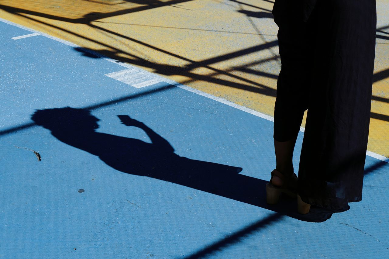 Low Section Of Person Standing By Shadow