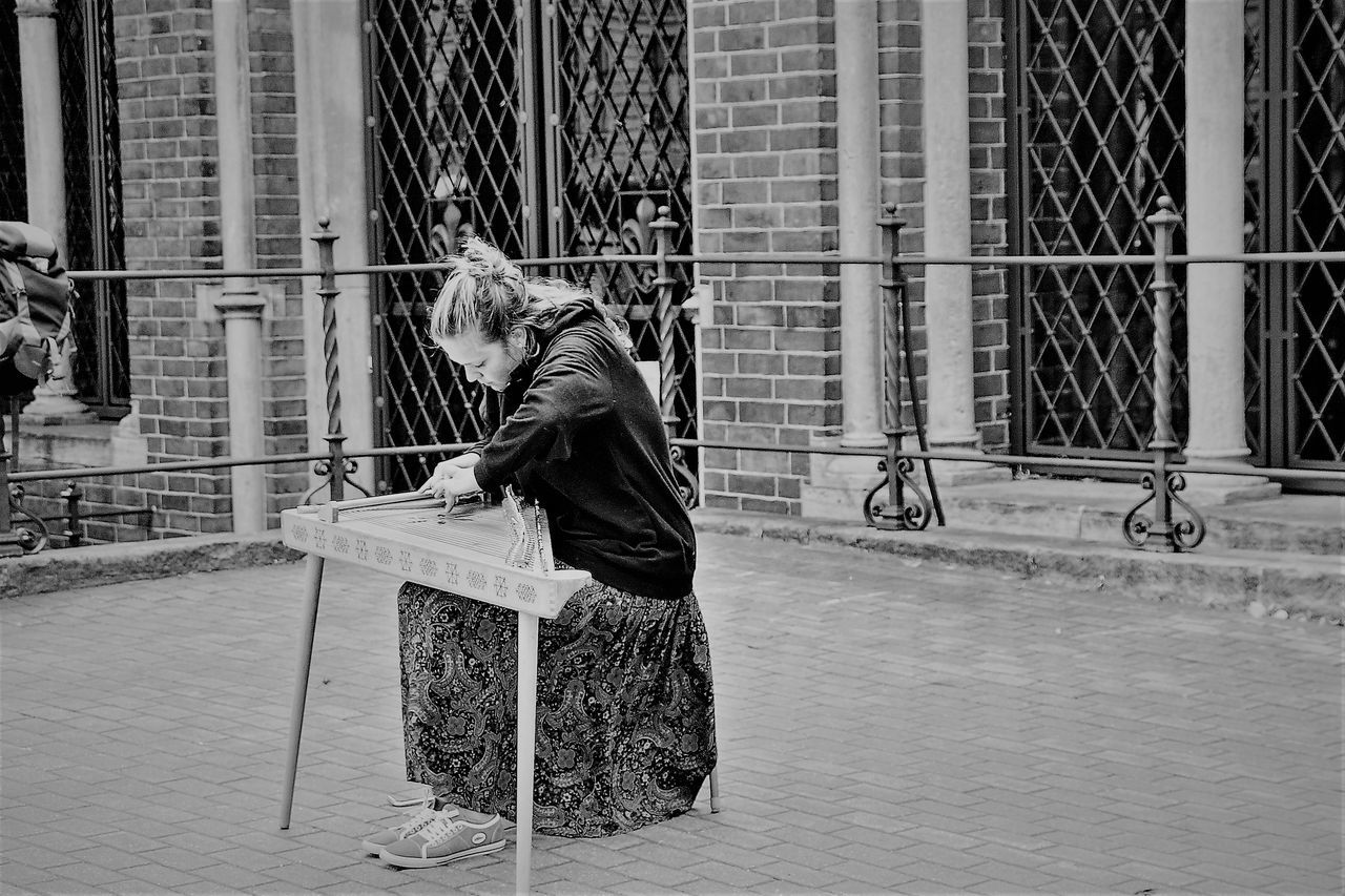 Ancient Stringed Musical Instrument Baltic States Building Exterior Day Full Length Lifestyles One Person Outdoors People Real People Sitting Street Musician. Streetphoto_bw The Street Photographer - 2017 EyeEm Awards Women Young Women
