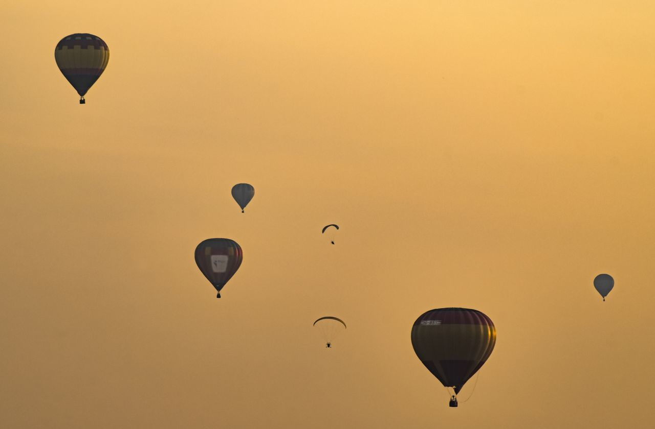 hot air balloon, flying, mid-air, adventure, sunset, ballooning festival, transportation, sky, air vehicle, balloon, silhouette, leisure activity, nature, outdoors, beauty in nature, celebration, extreme sports, parachute, clear sky, scenics, no people, day