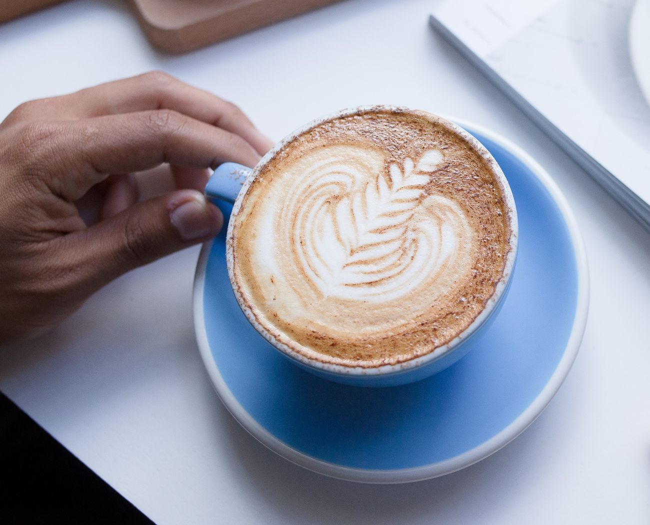 Blue Color Cappuccino Close-up Coffee - Drink Coffee Cup Day Drink Food And Drink Freshness Froth Art Frothy Drink Holding Human Body Part Human Hand Indoors  Latte Latte Morning One Person Real People Refreshment Saucer Table White Background