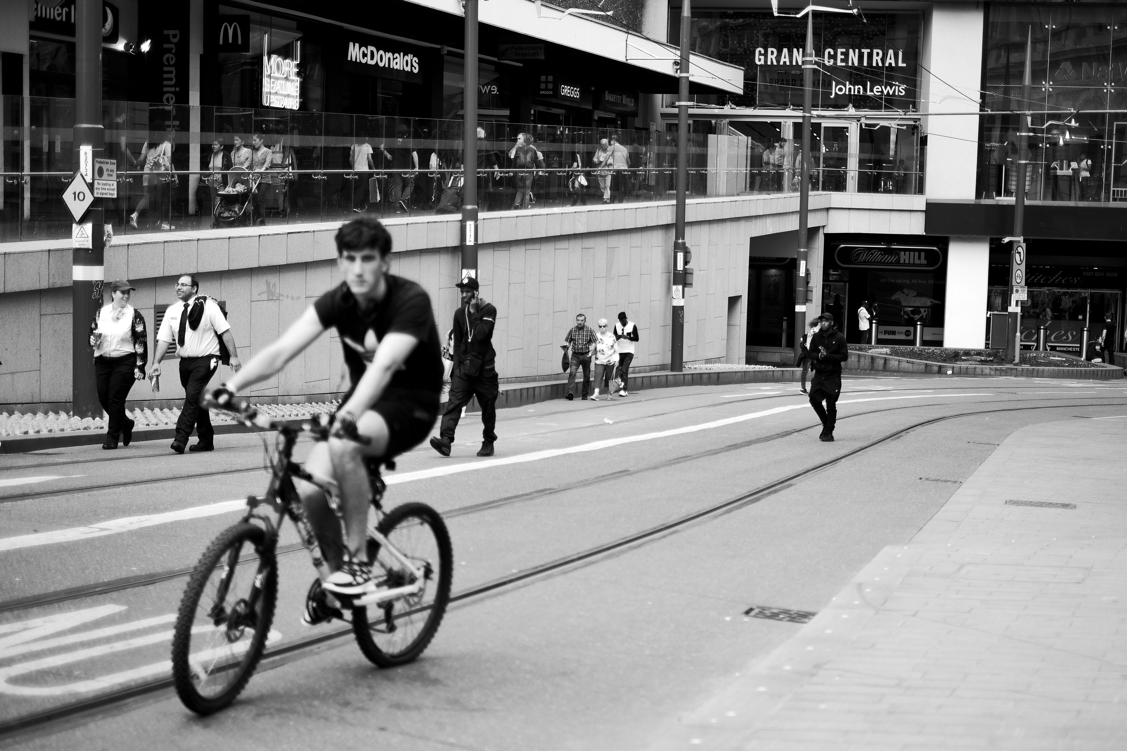 real people, bicycle, street, building exterior, men, architecture, built structure, transportation, riding, road, full length, city, cycling, women, outdoors, lifestyles, land vehicle, day, large group of people, adult, people
