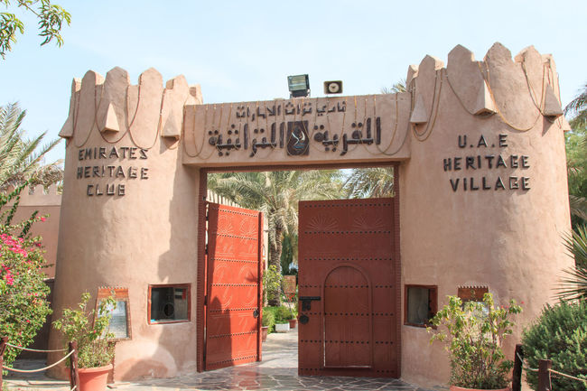 Abu Dhabi, UAE - October 10, 2014: Emirates Heritage Club and Heritage Village. Abu Dhabi Arabic Architecture Built Structure Clear Sky Communication Day Faith Islam Memories Outdoors People Sheik Zayed Mosque Text United Arab Emirates Western Script White Mosque