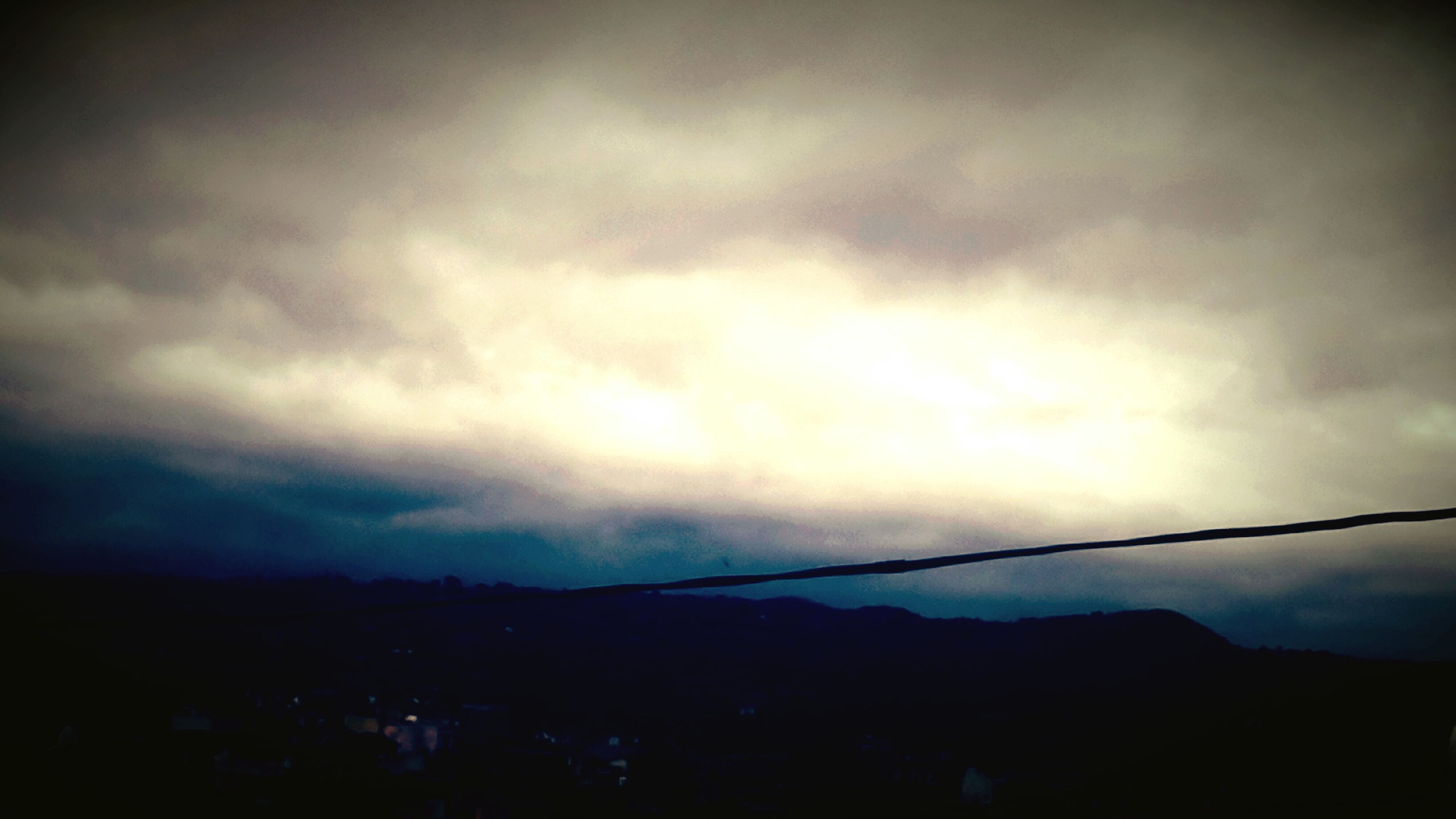 sky, cloud - sky, tranquility, scenics, tranquil scene, silhouette, cloudy, beauty in nature, mountain, weather, nature, landscape, dusk, overcast, low angle view, cloud, mountain range, idyllic, storm cloud, outdoors
