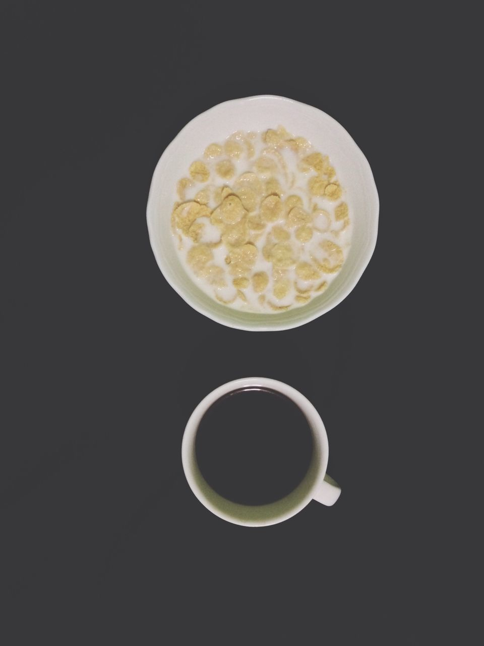 Overhead view of cornflakes and coffee over black background