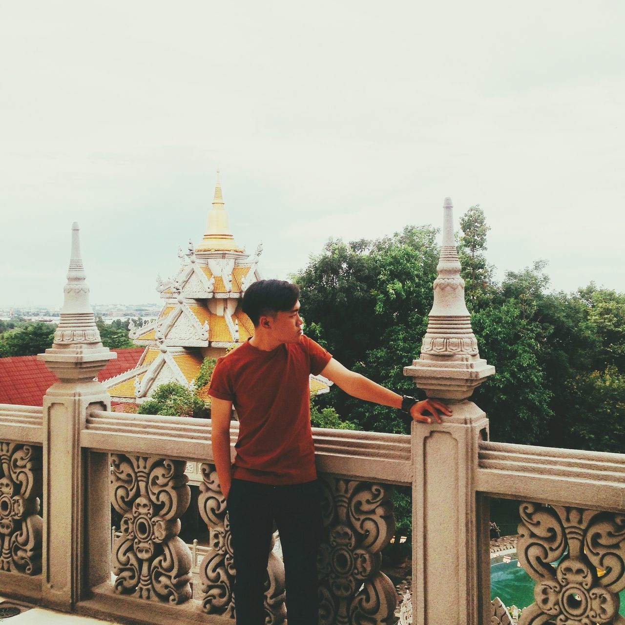 religion, real people, place of worship, spirituality, architecture, built structure, pagoda, building exterior, one person, travel destinations, lifestyles, rear view, sky, leisure activity, history, ancient, travel, tourism, tree, outdoors, standing, day, men, young adult