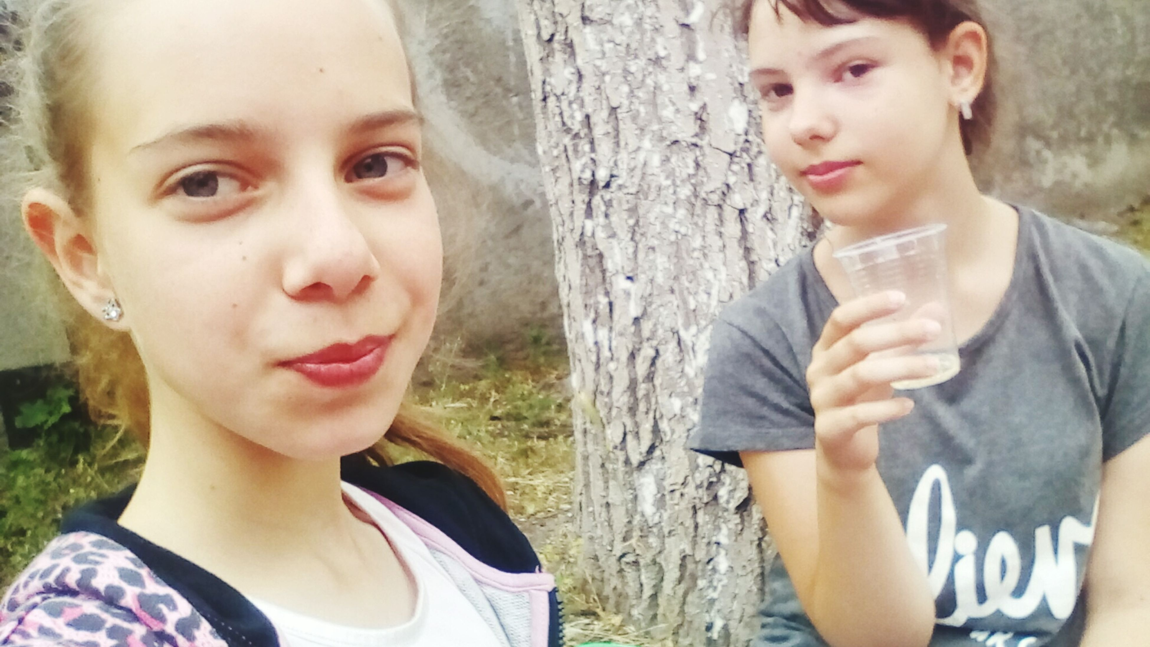 two people, childhood, looking at camera, real people, boys, leisure activity, portrait, casual clothing, elementary age, day, outdoors, lifestyles, togetherness, headshot, front view, focus on foreground, girls, standing, close-up, tree, bonding, young women, friendship, young adult, people