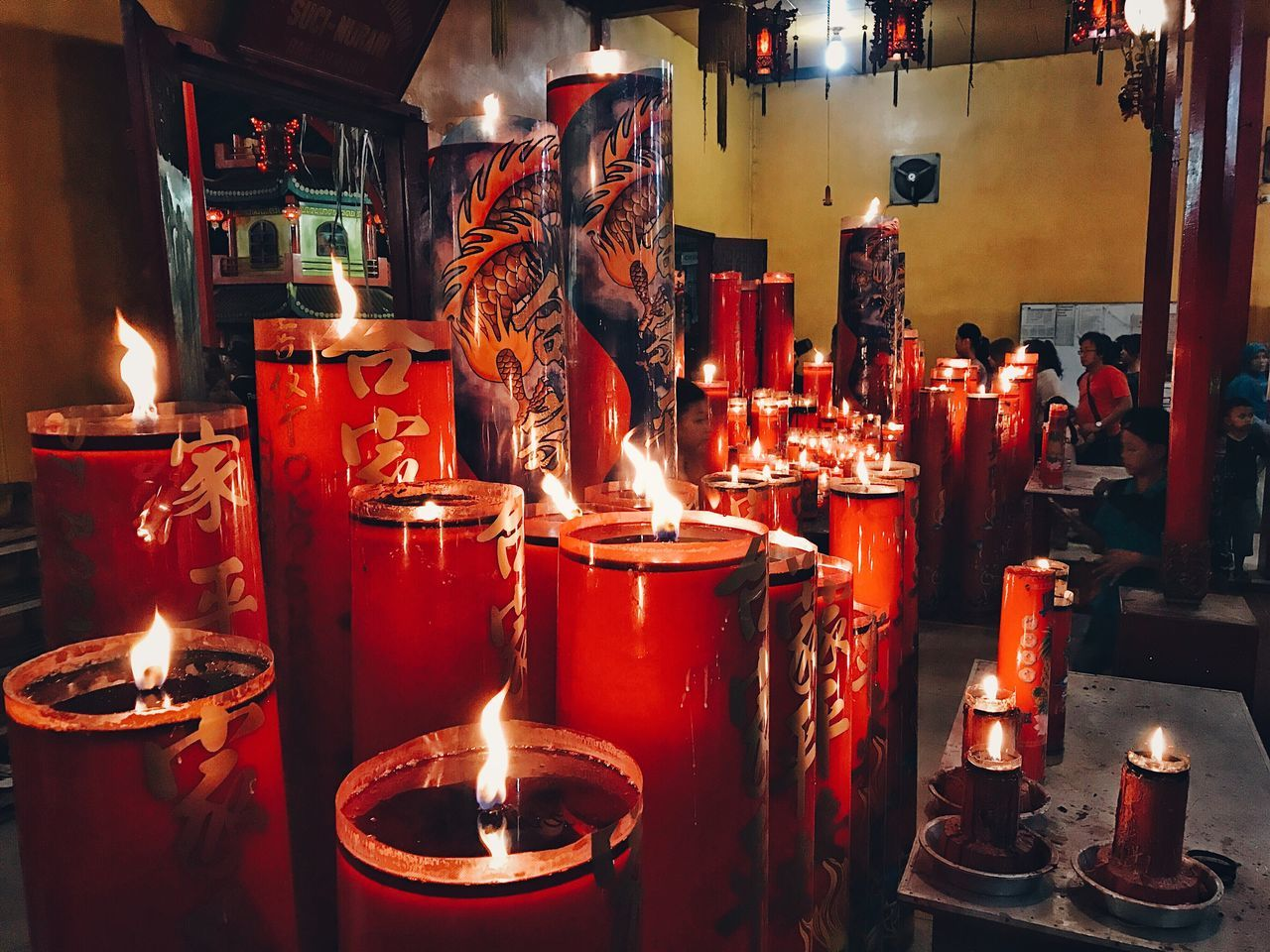 flame, candle, burning, heat - temperature, glowing, spirituality, religion, illuminated, real people, indoors, red, place of worship, standing, one person, people
