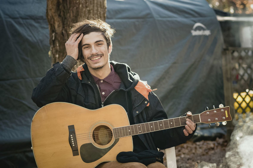 Casual Clothing Day Guitar Happiness Leisure Activity Lifestyles Music Musical Instrument Musician One Person Outdoors People Playing Plucking An Instrument Portrait Real People Sitting Smiling Young Adult Young Men Young Women