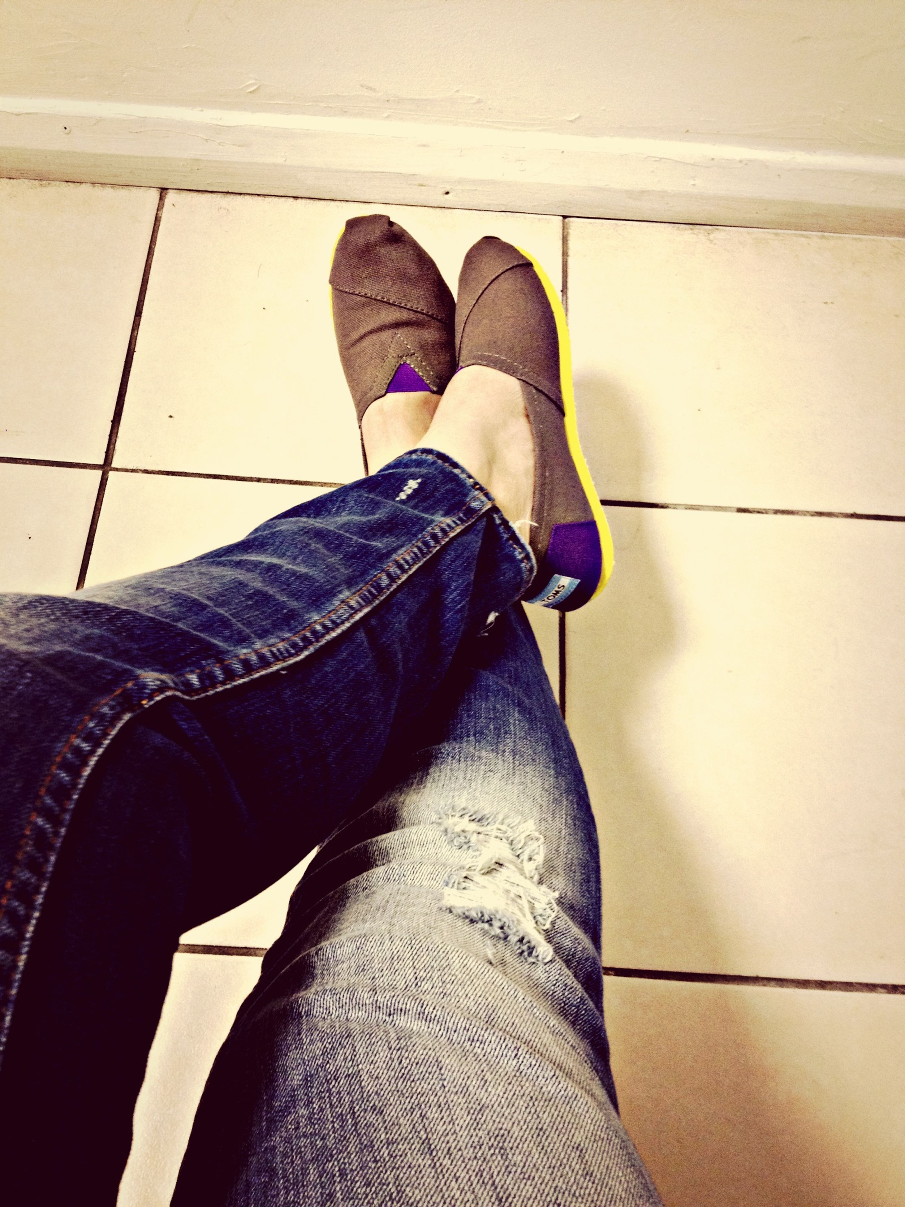 low section, person, shoe, jeans, lifestyles, personal perspective, footwear, standing, human foot, men, casual clothing, sitting, leisure activity, legs crossed at ankle, fashion, denim, relaxation