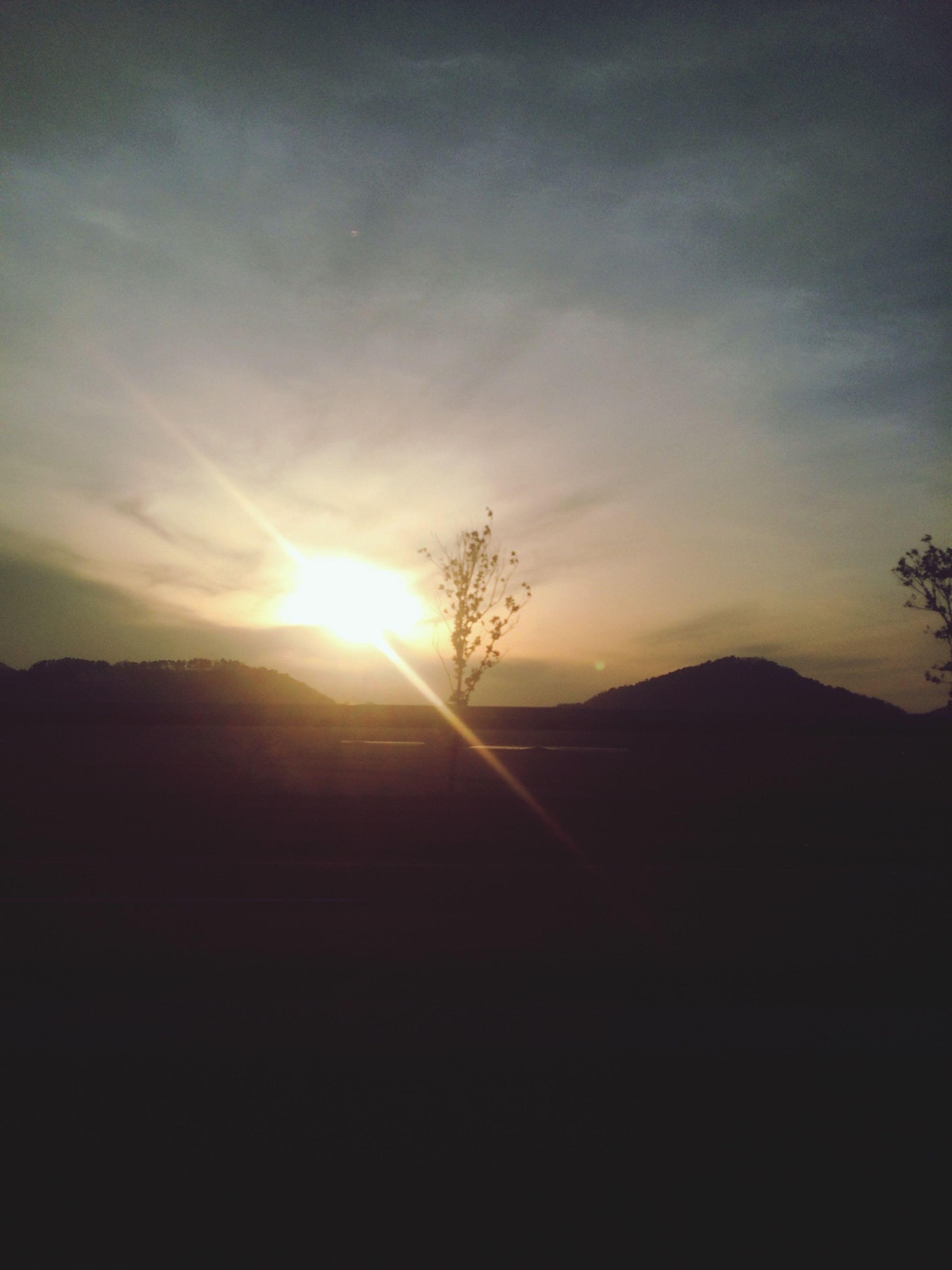 sunset, silhouette, sun, tranquil scene, tranquility, scenics, beauty in nature, mountain, landscape, sky, sunlight, nature, sunbeam, idyllic, mountain range, lens flare, non-urban scene, dark, outdoors, no people