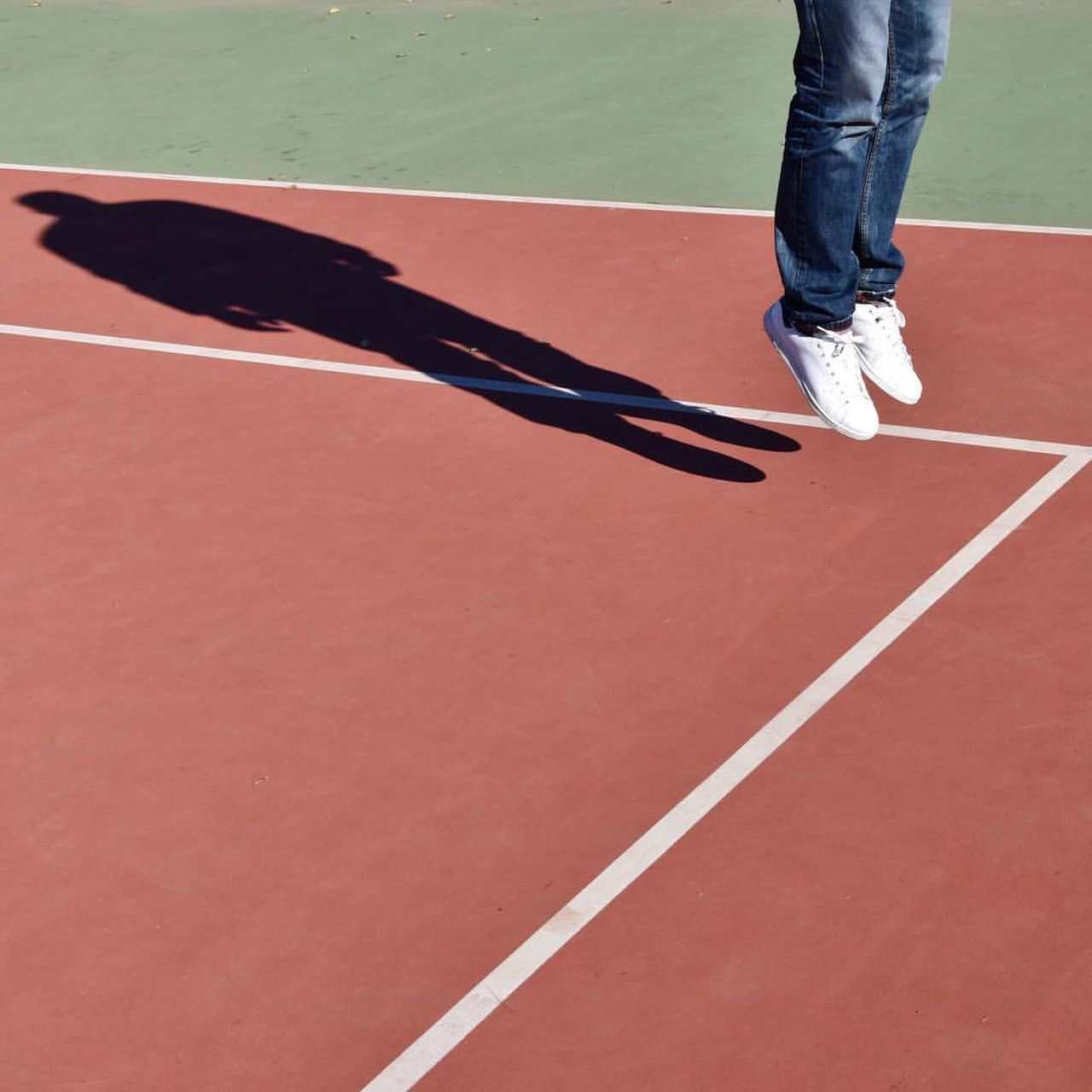 Low Section Of Man Jumping On Tennis Court