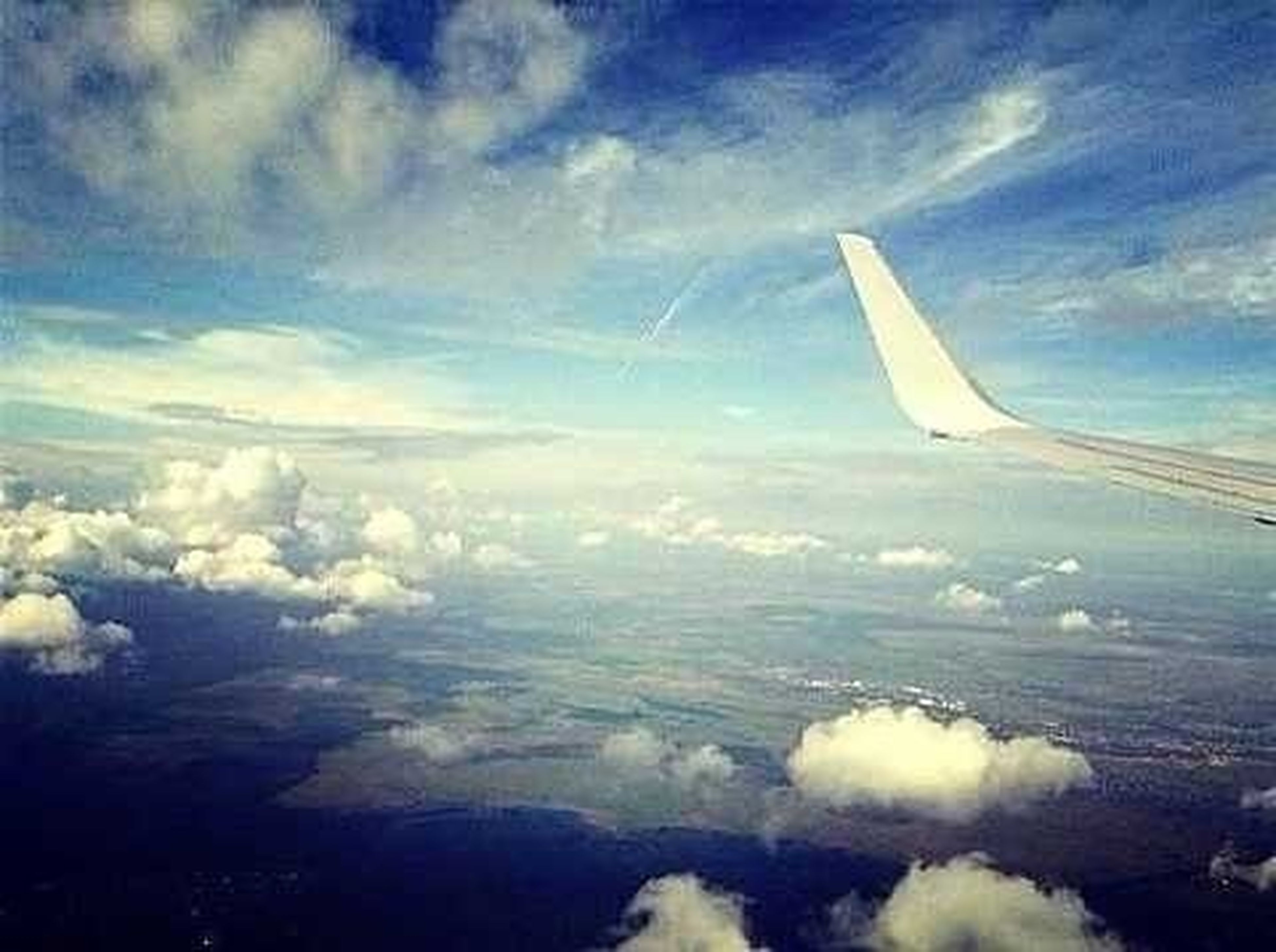 flying, airplane, aircraft wing, air vehicle, aerial view, sky, transportation, cloud - sky, beauty in nature, part of, scenics, cropped, mid-air, nature, travel, mode of transport, cloud, blue, tranquil scene, sea