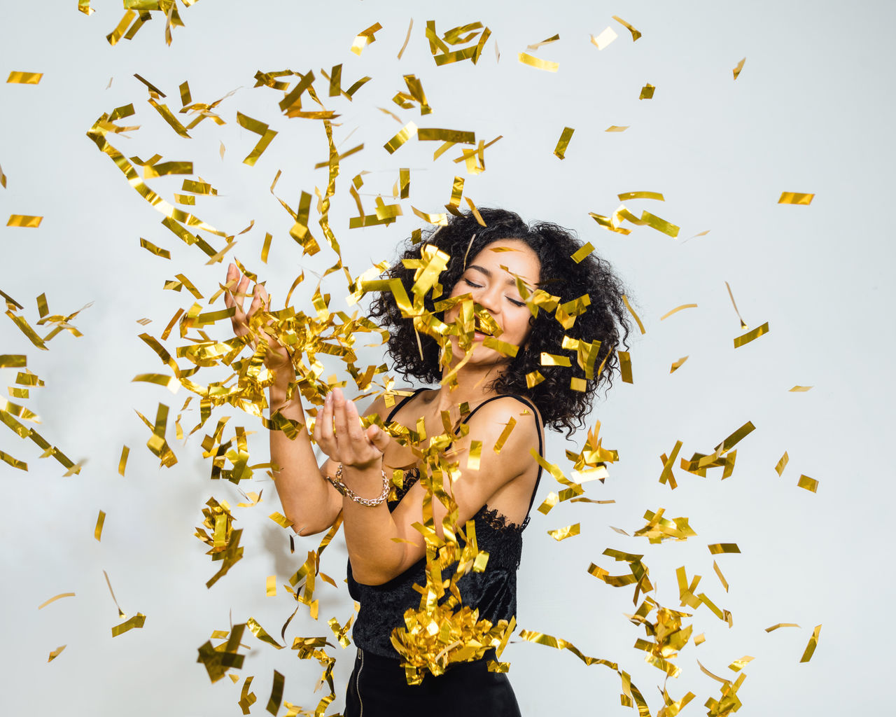 Adults Only African American Anniversary Birthday Brunette Candid Celebration Confetti Eve Event Female Fun Golden Happy Indoors  New Year One Person Party People Smiling Throwing  Woman Young Adult