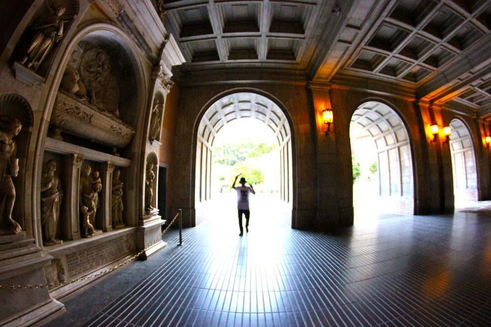 Man enters the courtyard of the temple through the arch. Arch Architectural Column Architectural Feature Architecture Building Building Exterior Built Structure Casual Clothing Column Come In Diminishing Perspective Entrance Fisheye Full Length Lamps Leisure Activity Sculpture Sculptures Temple The Way Forward Tunnel My Favorite Photo