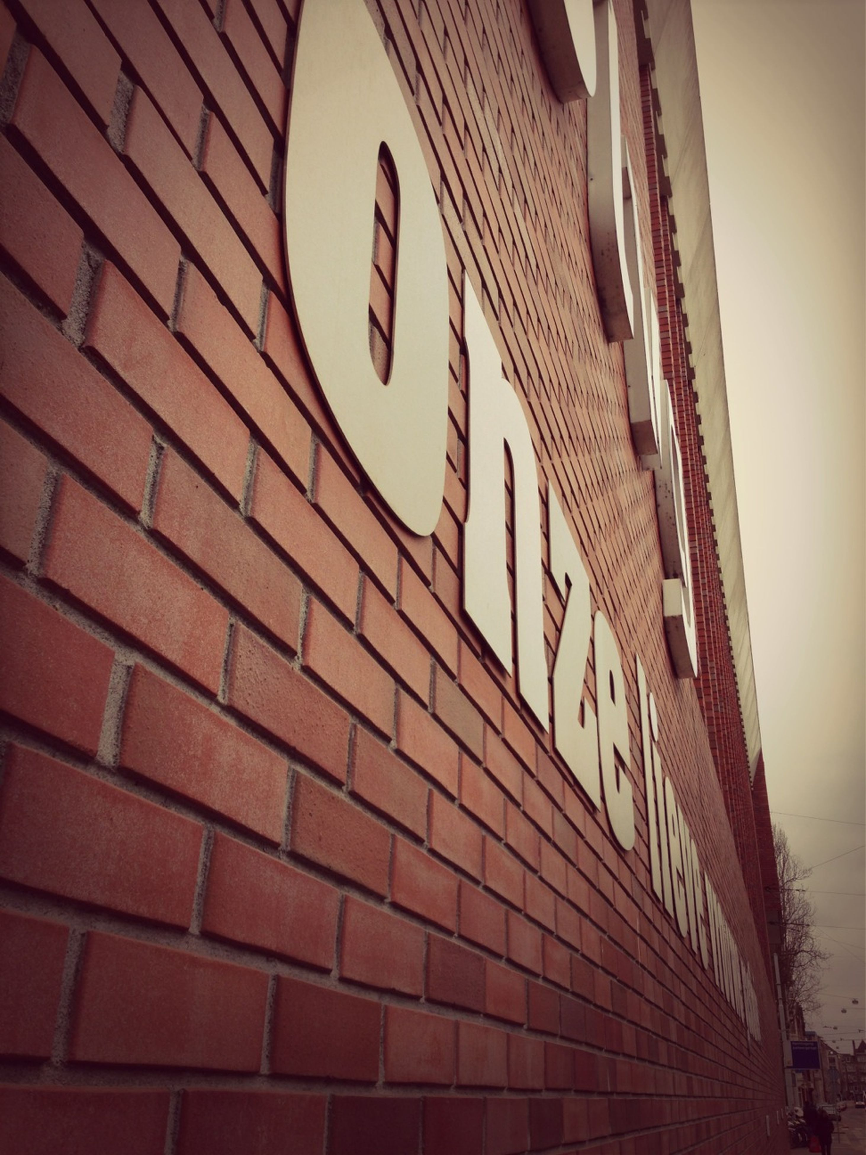 architecture, built structure, building exterior, low angle view, building, window, brick wall, city, no people, pattern, outdoors, day, residential building, sky, residential structure, modern, full frame, wall - building feature, repetition, text