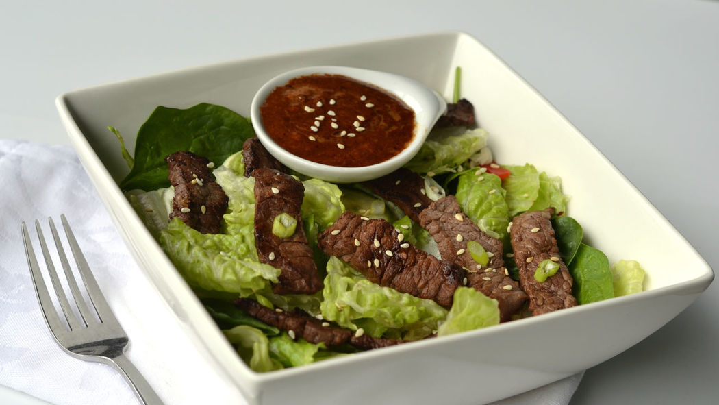 Asian Steak Salad; served in a square white bowl with dressing on the side. Appetiser Appetizer Asian Beef Salad Asian Dressing Asian Food Bowl Close Up Close-up Cucumber First Course Food Food And Drink Grilled Steak Strips Healthy Eating Keto Ketogenic Diet Salad Lunch Red Pepper Romaine Lettuce Salad Salad Dressing Sesame Seeds Steak Steak Salad White
