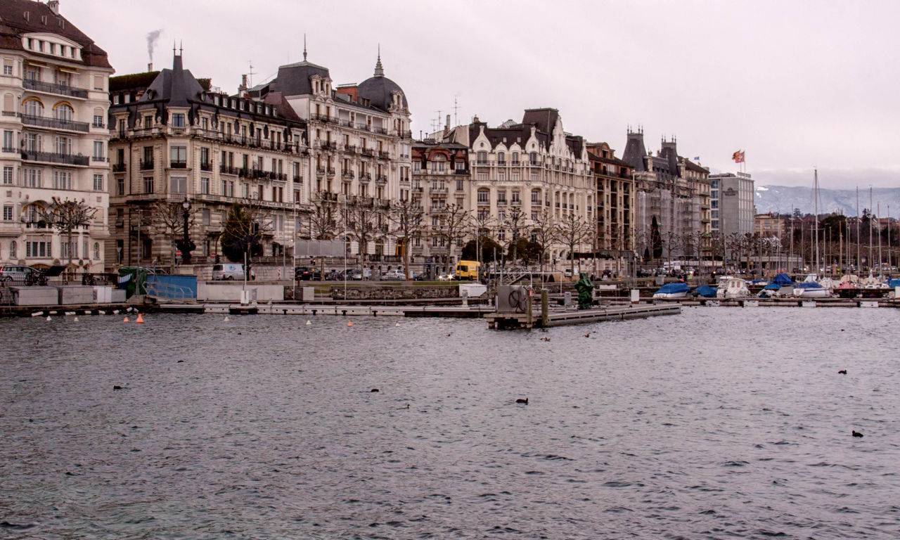 Geneva Architecture Building Exterior Buildings, Old, Historical, City, Town, Water, Boats, Hotels Culture Façade Famous Place Geneva, Switzerland, Europe, European, Geneva Lake, Lake, Water, Seagulls, Birds, Mountains, Cloudy, Clouds Incidental People Large Group Of People Old Town Outdoors People In The Background Residential District Tourism Tourist Town Square