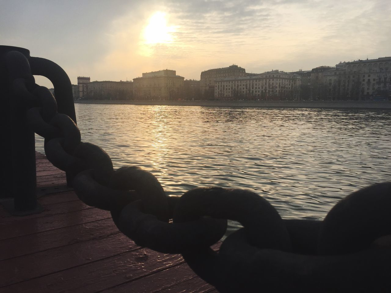 sunset, water, sky, architecture, river, built structure, building exterior, togetherness, cloud - sky, strength, outdoors, city, close-up, flexibility, human hand, day, nature, people
