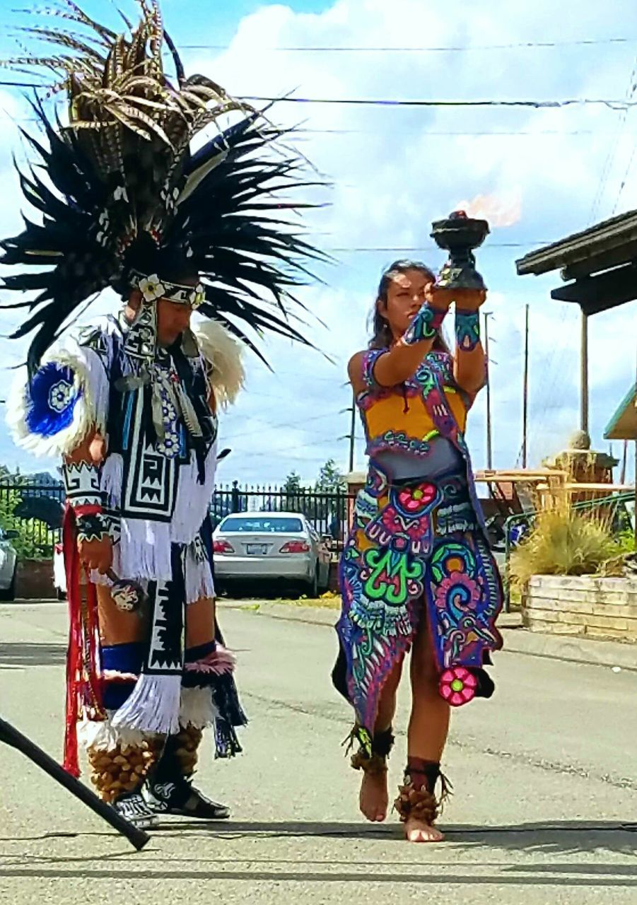 costume, celebration, carnival - celebration event, real people, lifestyles, cultures, leisure activity, performance, headdress, carnival, arts culture and entertainment, enjoyment, dancer, day, tradition, full length, feather, outdoors, traditional dancing, stage costume, headwear, women, men, young women, adult, people
