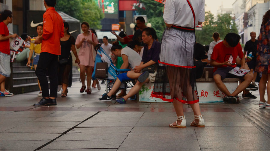 Dress Pedestrian Walkway Sitting Outside Urban Lifestyle Wuhan China Crowd Large Group Of People Leisure Activity Lifestyles Low Section Outdoors Real People Red Color Shoes Walking Women