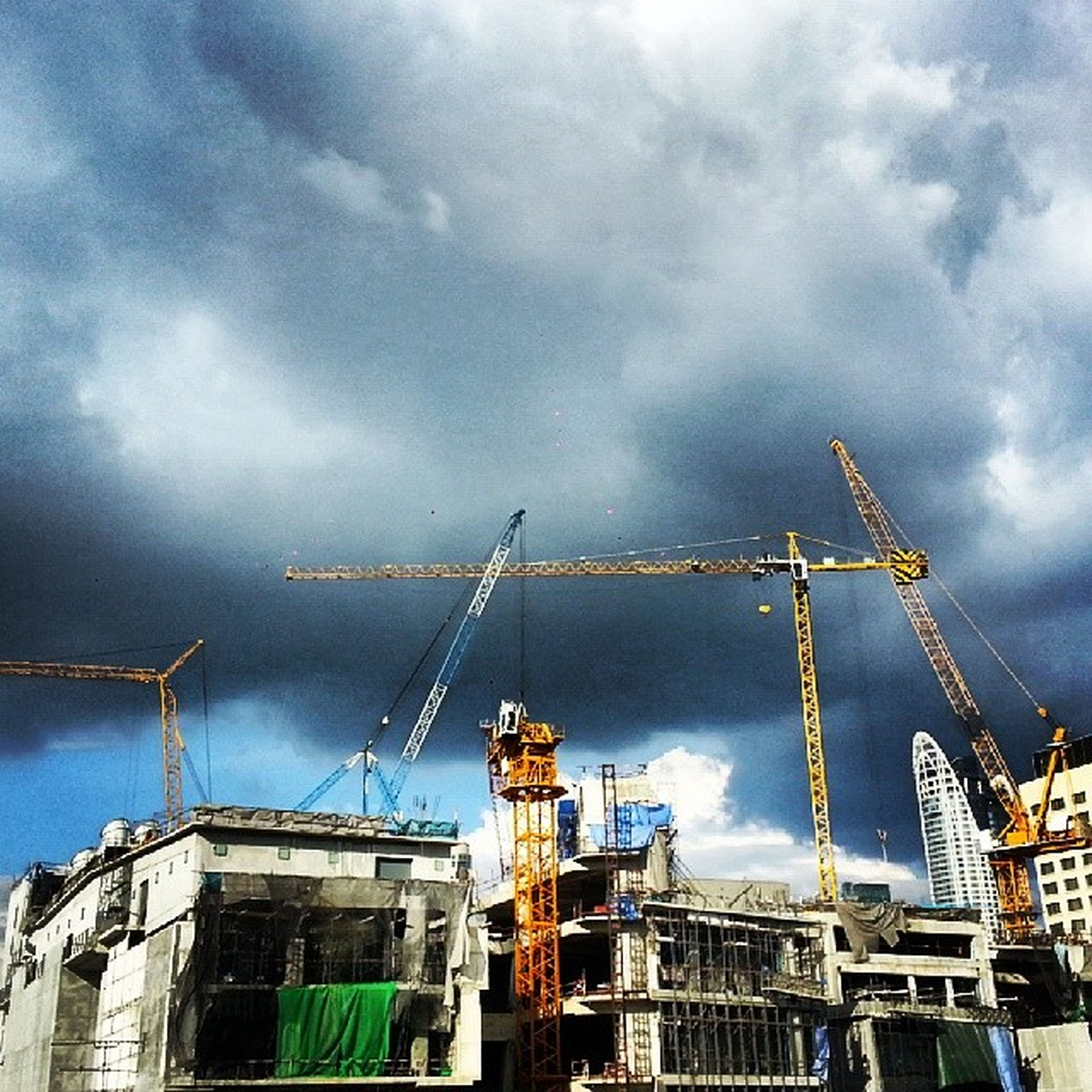 architecture, built structure, building exterior, sky, cloud - sky, low angle view, cloudy, construction site, crane - construction machinery, development, industry, weather, construction, cloud, factory, incomplete, day, crane, overcast, building