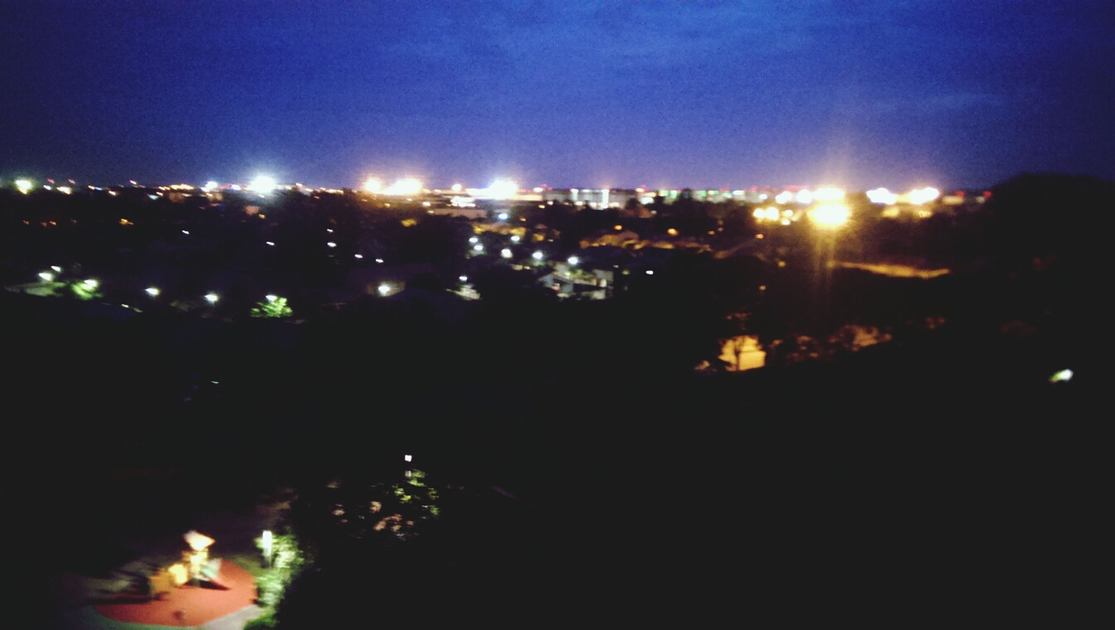 illuminated, night, building exterior, city, built structure, architecture, cityscape, sky, glowing, dark, residential structure, residential building, high angle view, residential district, light - natural phenomenon, outdoors, lighting equipment, city life, street light, dusk