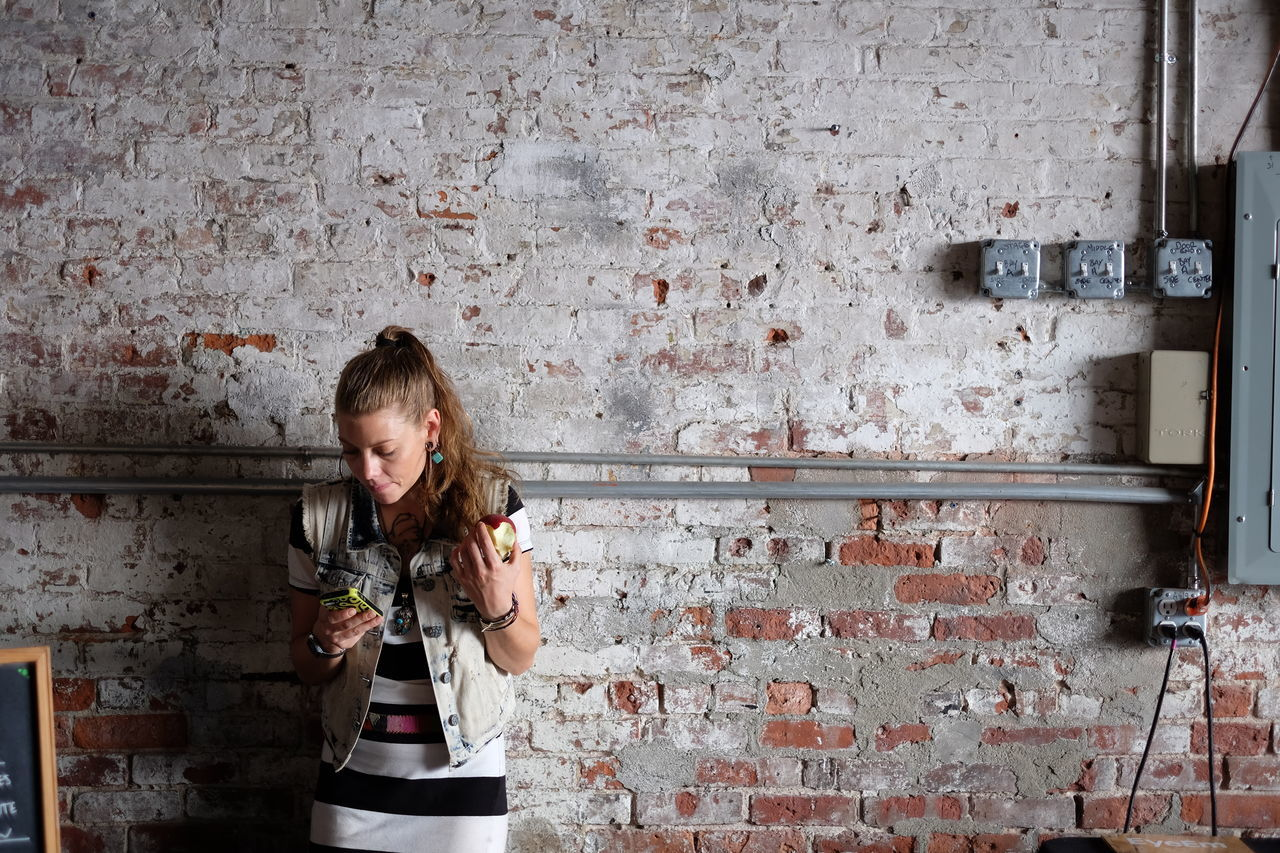 brick wall, one person, childhood, standing, holding, real people, built structure, indoors, child, children only, day, people, adult
