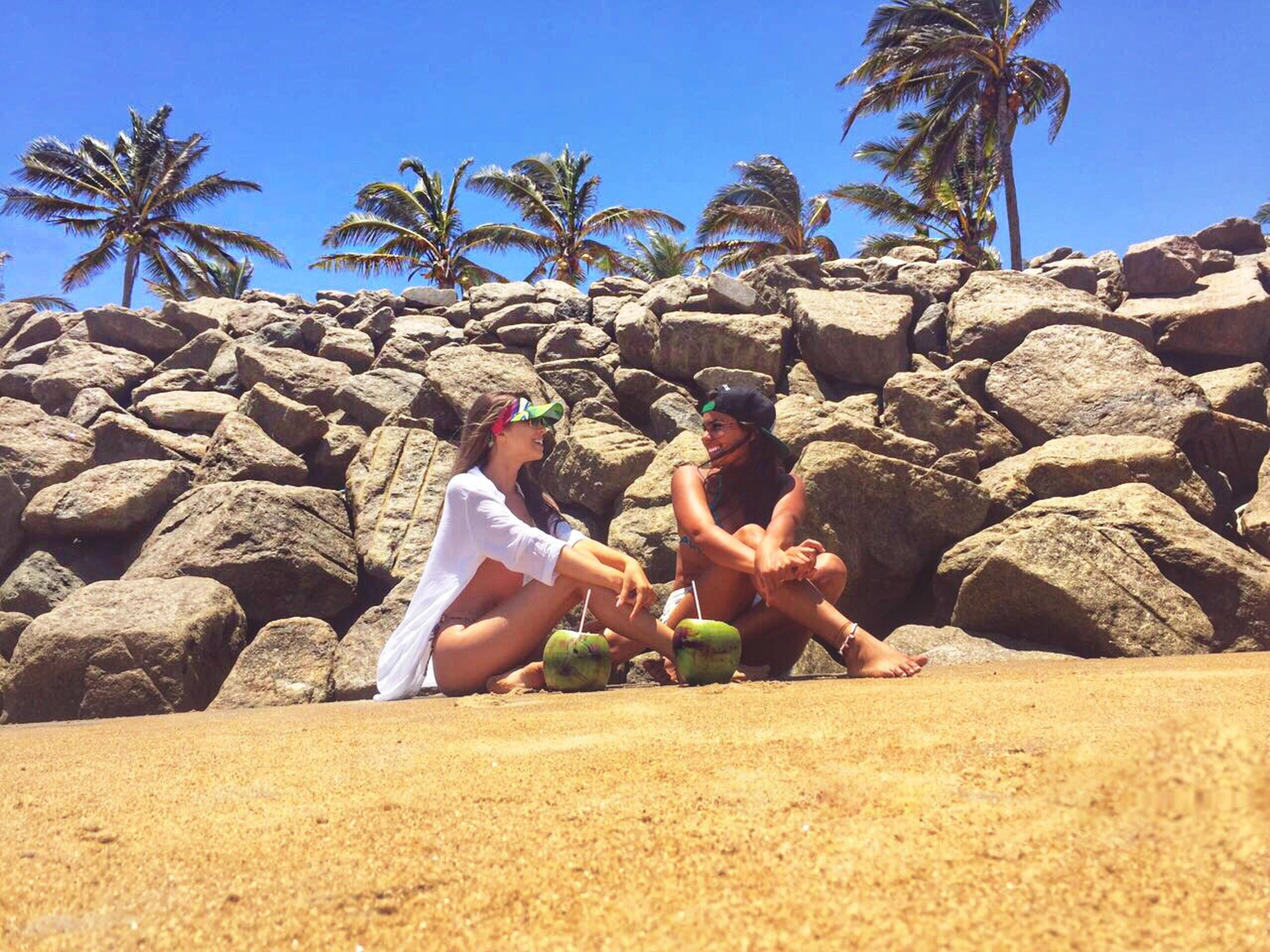 relaxation, vacations, sunlight, sitting, outdoors, two people, beach, togetherness, leisure activity, rock - object, palm tree, summer, day, sea, adults only, adult, nature, healthy eating, people, beauty in nature