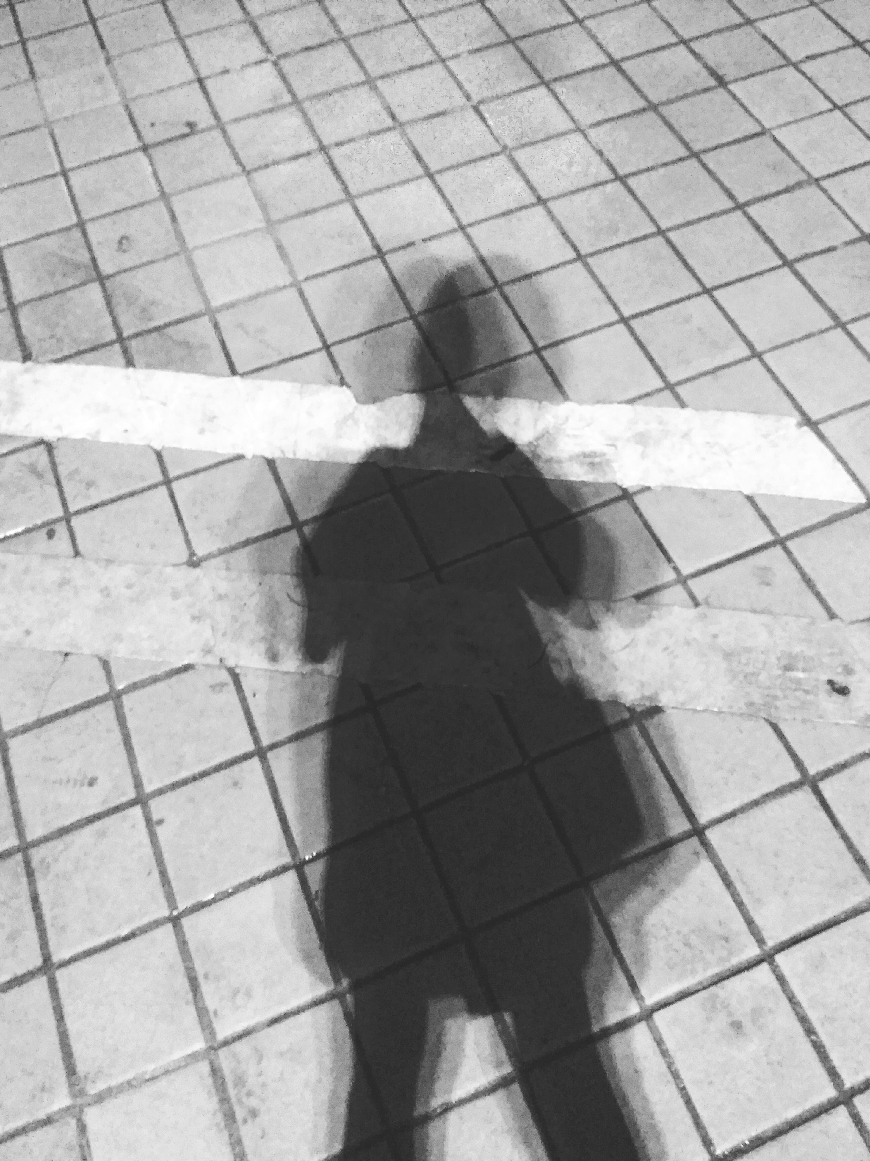 real people, focus on shadow, high angle view, lifestyles, shadow, sunlight, tiled floor, day, one person, outdoors, men