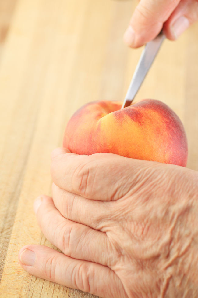 Cutting a peach with a paring knife Close-up Copy Space Fingers Food Preparation Fresh Fruit Hands Healthy Eating Holding Indoors  Man Natural Light One Person Paring Knife Peach Raw Food Senior Using Tool Vertical Wood - Material Wrinkled Skin