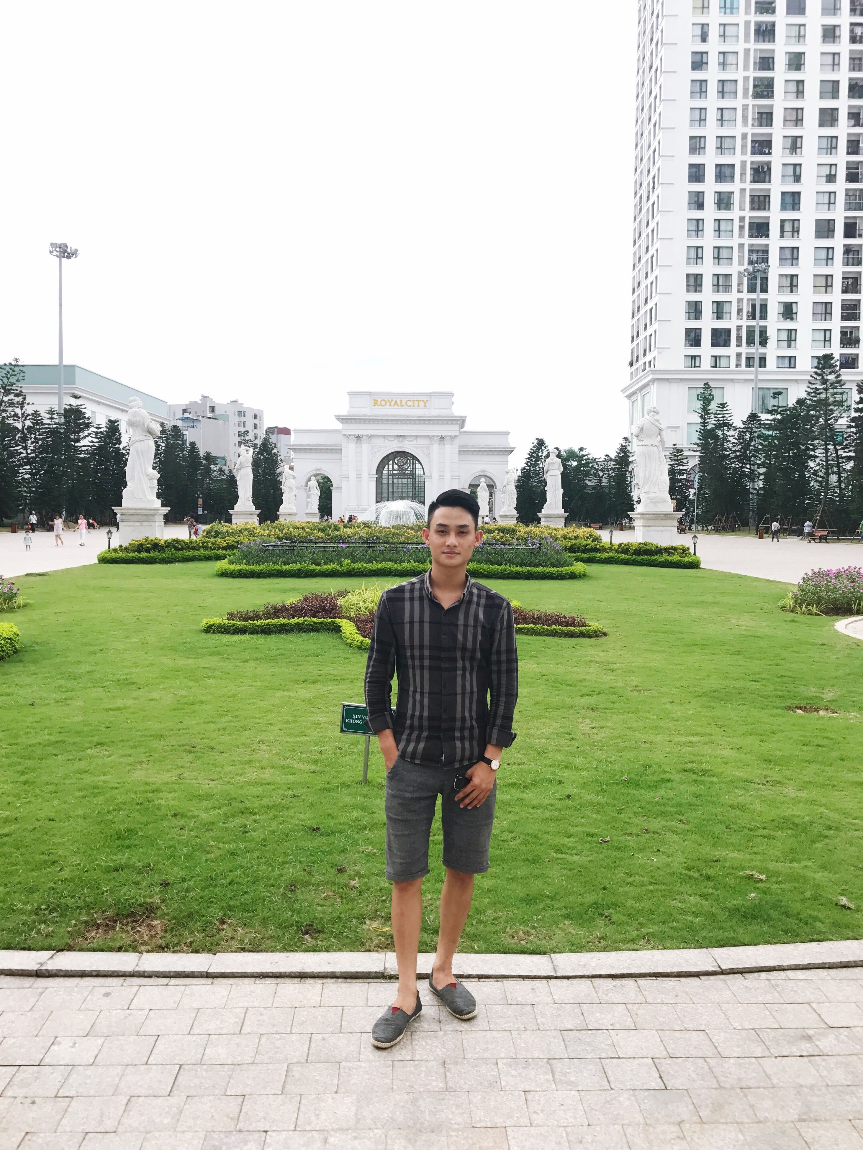 architecture, building exterior, built structure, real people, outdoors, day, young adult, casual clothing, full length, front view, tourism, leisure activity, grass, lawn, young men, tree, lifestyles, travel destinations, standing, looking at camera, green color, young women, portrait, one person, growth, clear sky, city, smiling, nature